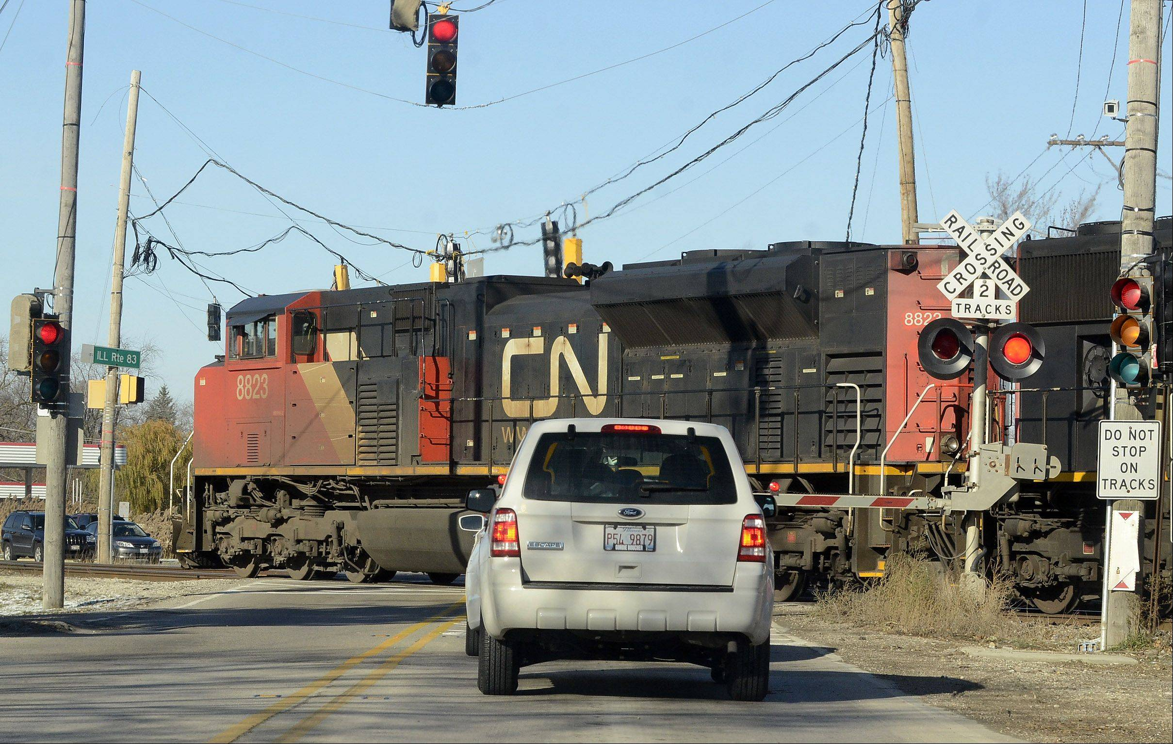 Traffic backs up as a freight train travels the crossing at routes 83 and 137 in Grayslake. Village officials are urging residents to contact state and federal lawmakers for help in dealing with long traffic delays caused by train stoppages.