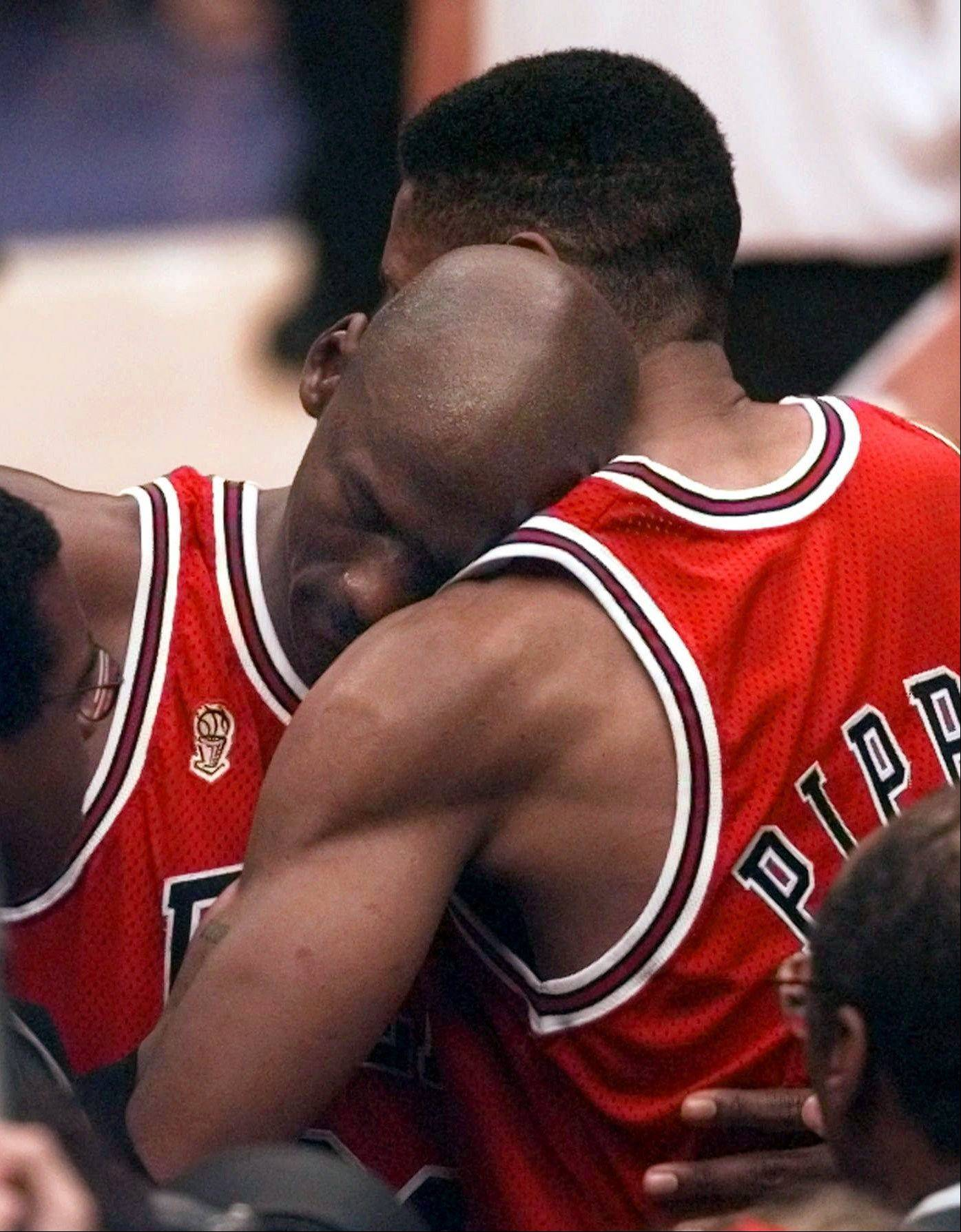 Bulls guard Michael Jordan collapses in the arms of teammate Scottie Pippen, right, at the end of Game 5 of the NBA Finals against the Utah Jazz in 1997, in Salt Lake City. Jordan, fighting flu-like symptoms, scored 38 points to help the Bulls win the game. Jordan gave his shoes to a ball boy, who is now putting them up for auction.