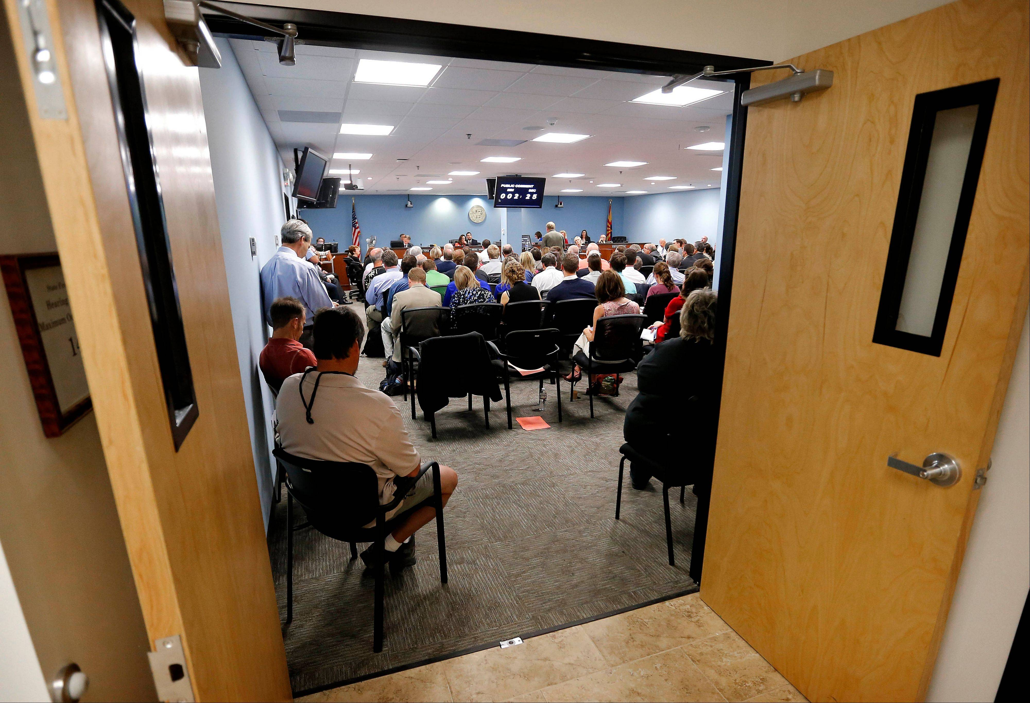 The meeting room is filled during a hearing at the Arizona Corporation Commission on Wednesday in Phoenix. The commission met to discuss rooftop solar power and to hear testimony from a series of residents who packed the room to express their opinions.