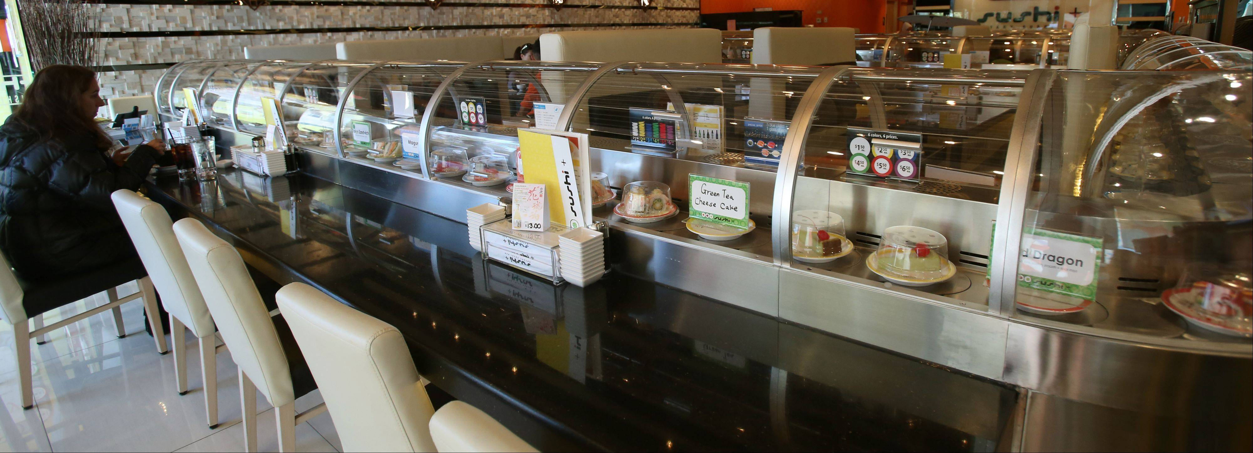A seemingly endless stream of plates passes by diners on the rotary sushi bar at Sushi + Rotary Sushi Bar in Aurora.
