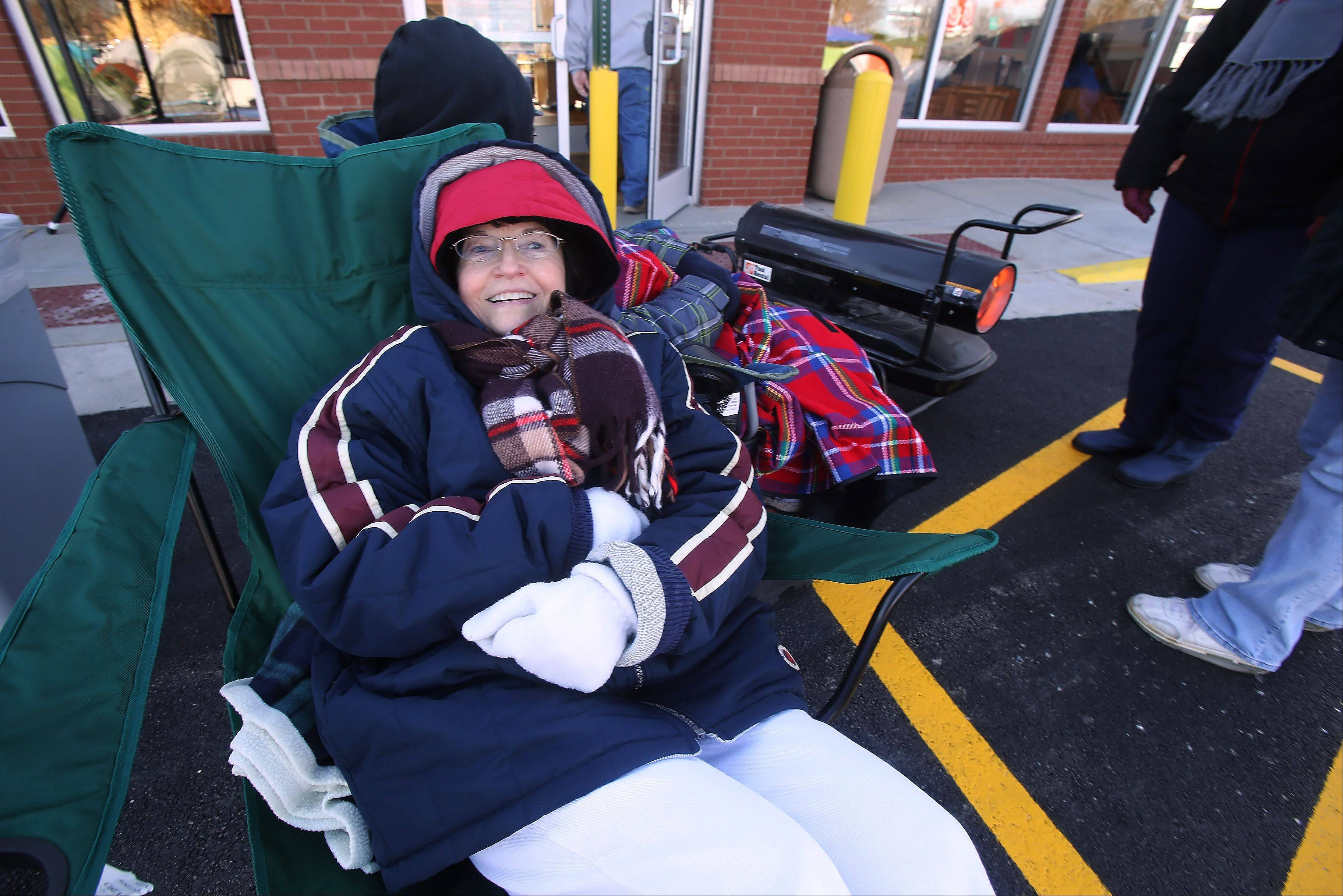 Bundled for the cold, Carol Durietz of Vernon Hills waits in line near a heater Wednesday outside the new Chick-fil-A location in Vernon Hills. The first 100 customers waiting in line when the restaurant opens Thursday will receive a free meal a week for the next year.