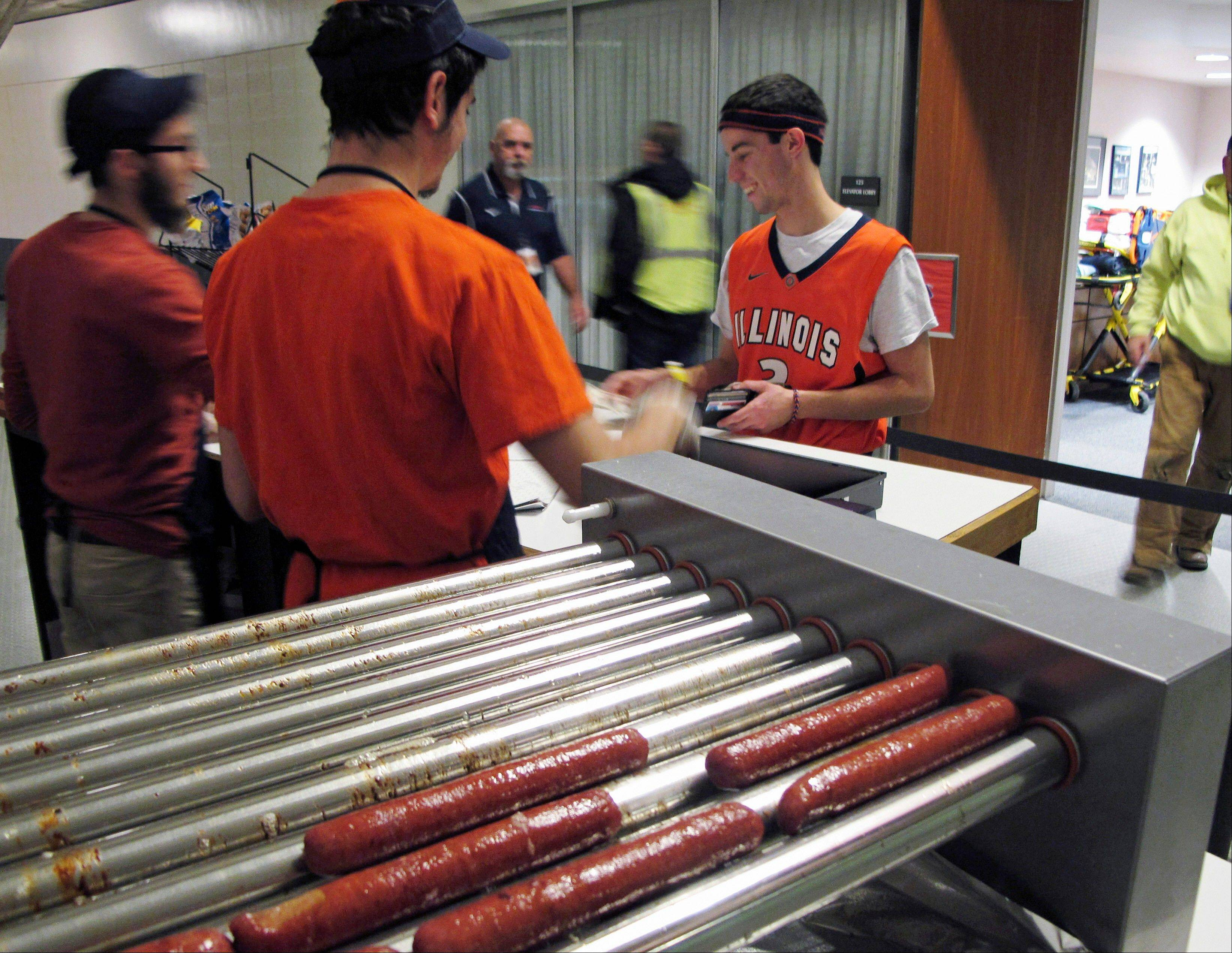 An Illini basketball fan buys a kosher hot dog from Mordy Kurtz, left, and Yosef Peysin on Sunday at the kosher food stand at the university's State Farm Center basketball arena in Champaign.