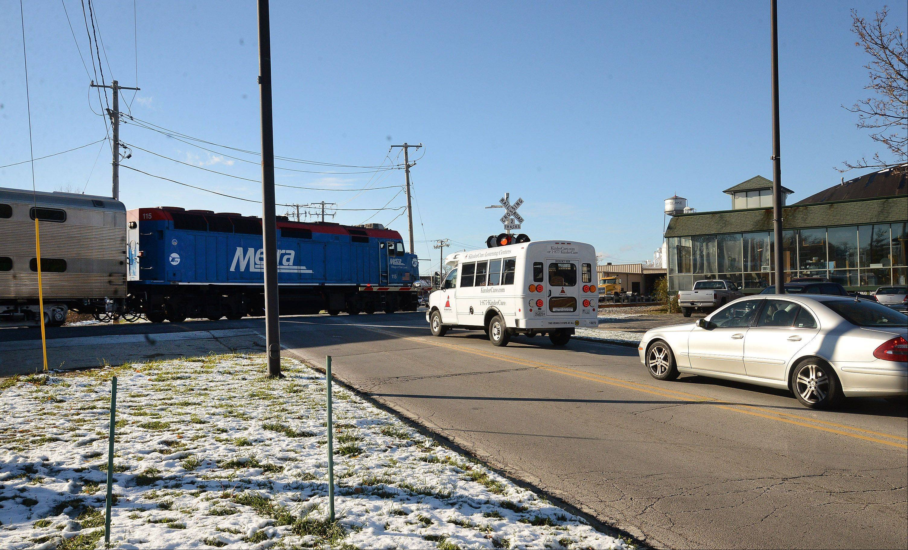 A Metra commuter train passes through downtown Grayslake as traffic backs up along Center Street. Village officials are urging residents to contact state and federal lawmakers for help in dealing with long traffic delays caused by train stoppages.