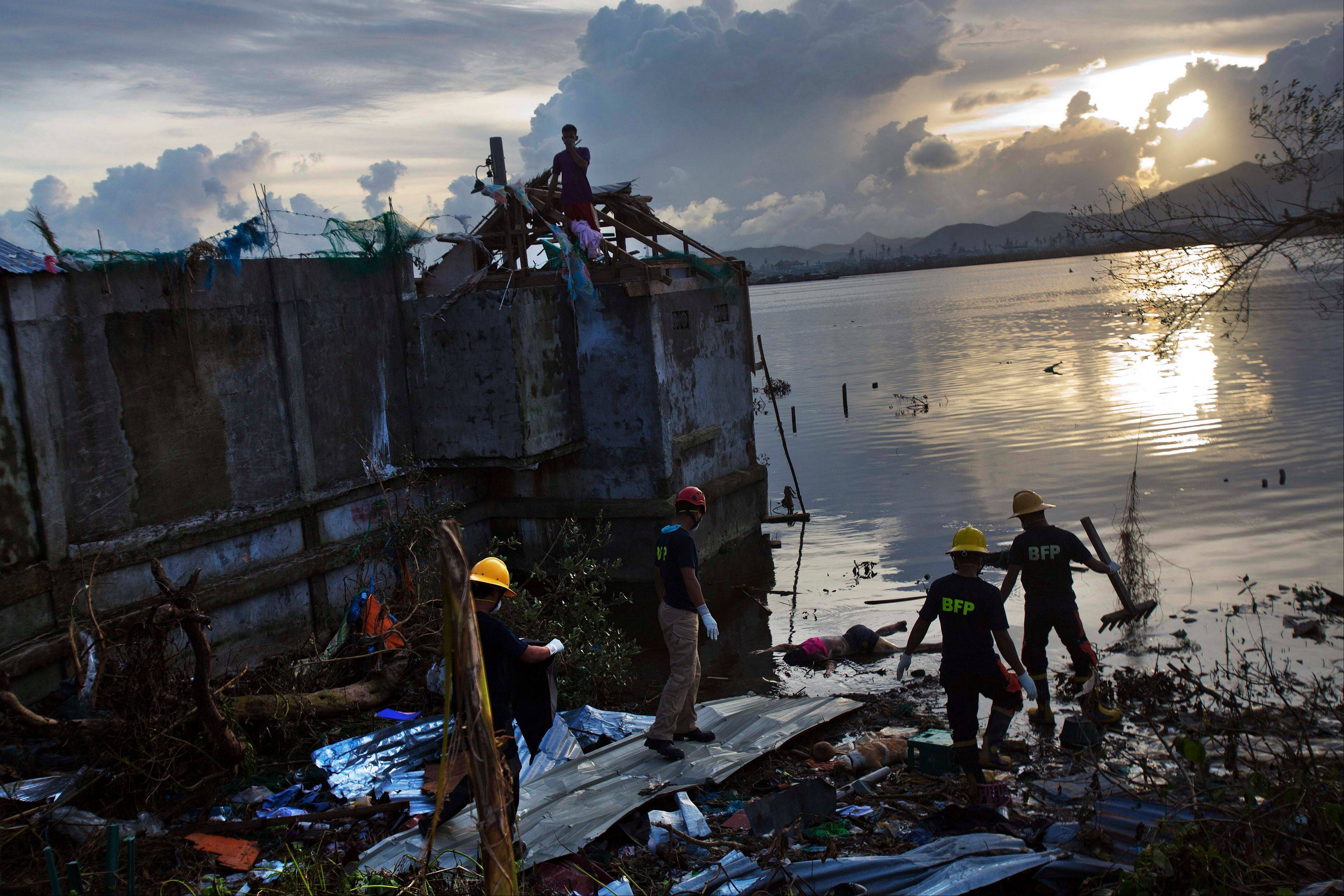 A Philippines rescue team wades into floodwaters to retrieve a body in the Typhoon Haiyan ravaged city of Tacloban, central Philippines on Wednesday, Nov. 13, 2013.