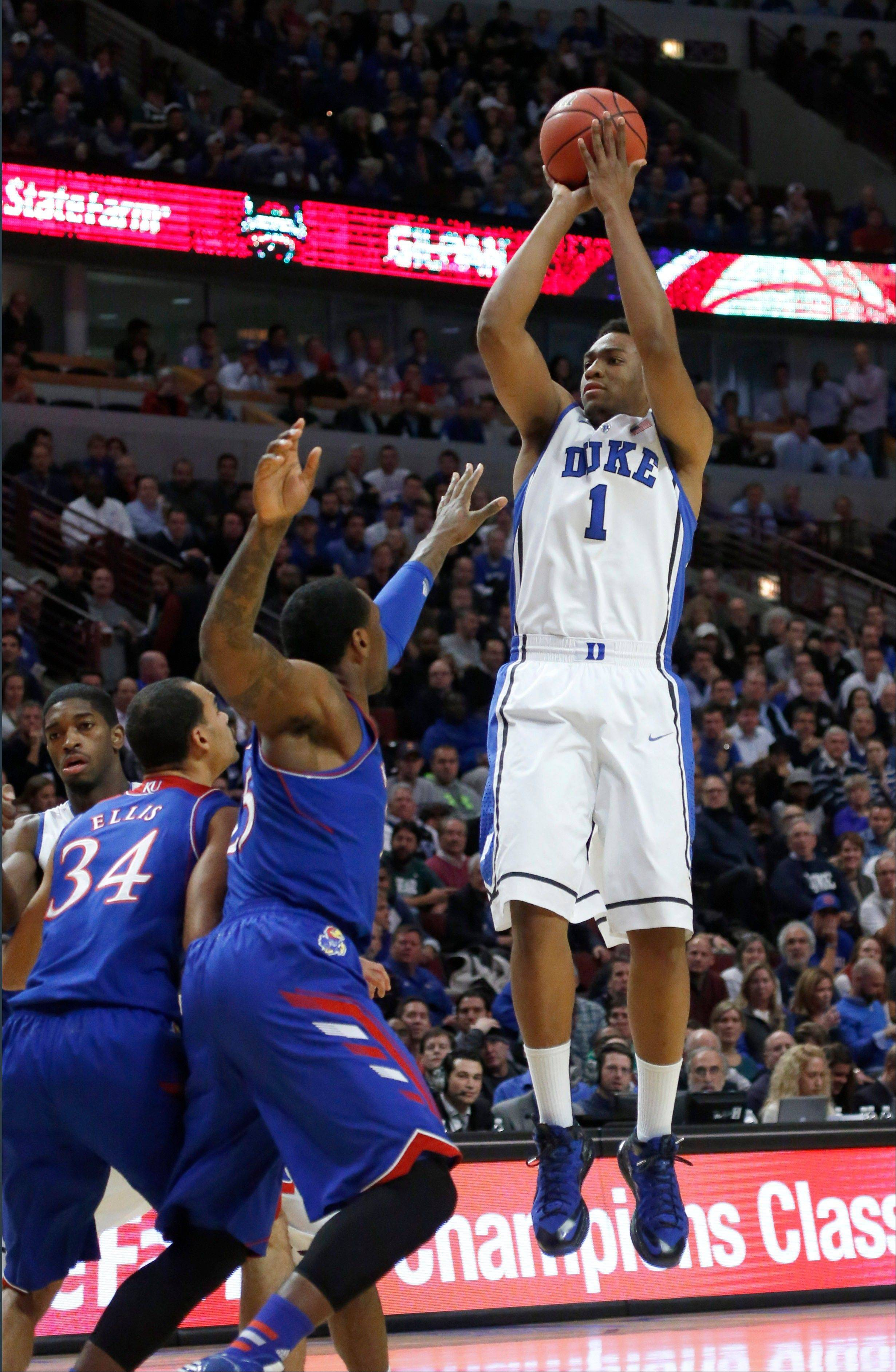 Duke forward Jabari Parker (1) shoots over Kansas forward Perry Ellis (34) and Tarik Black during the first half of an NCAA college basketball game on Tuesday, Nov. 12, 2013, in Chicago.