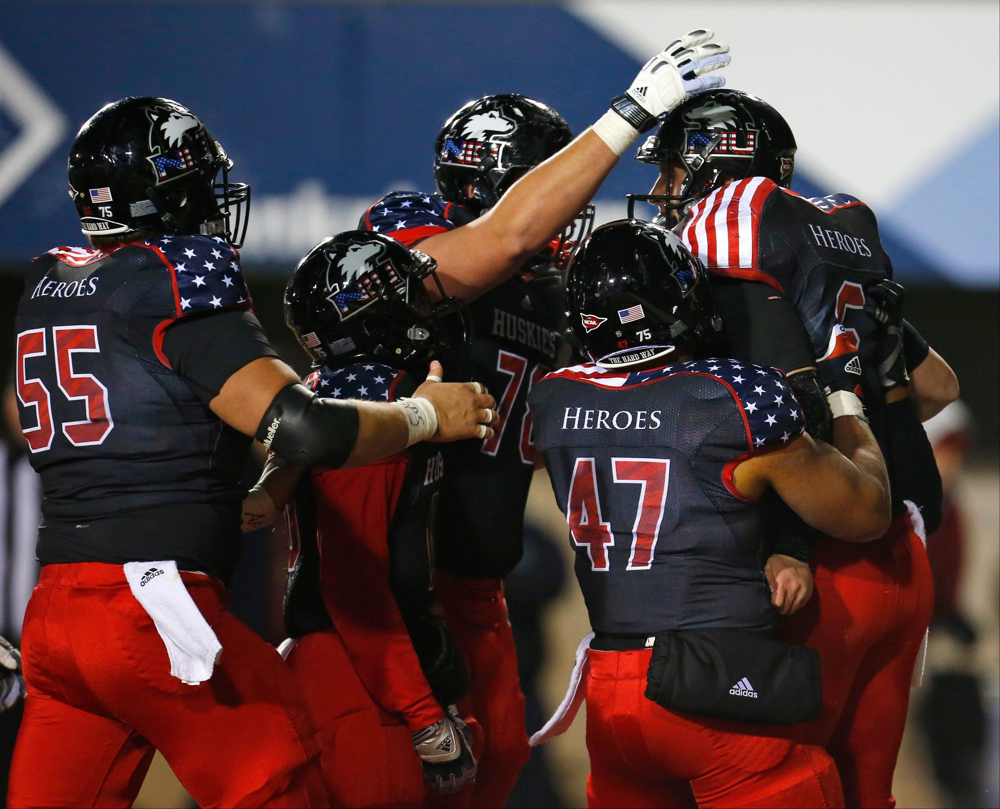 Northern Illinois quarterback Jordan Lynch, right, celebrates with teammates after scoring a touchdown during the second half of an NCAA college football game against Ball State on Wednesday, Nov. 13, 2013, in DeKalb, Ill. Northern Illinois won 48-27.