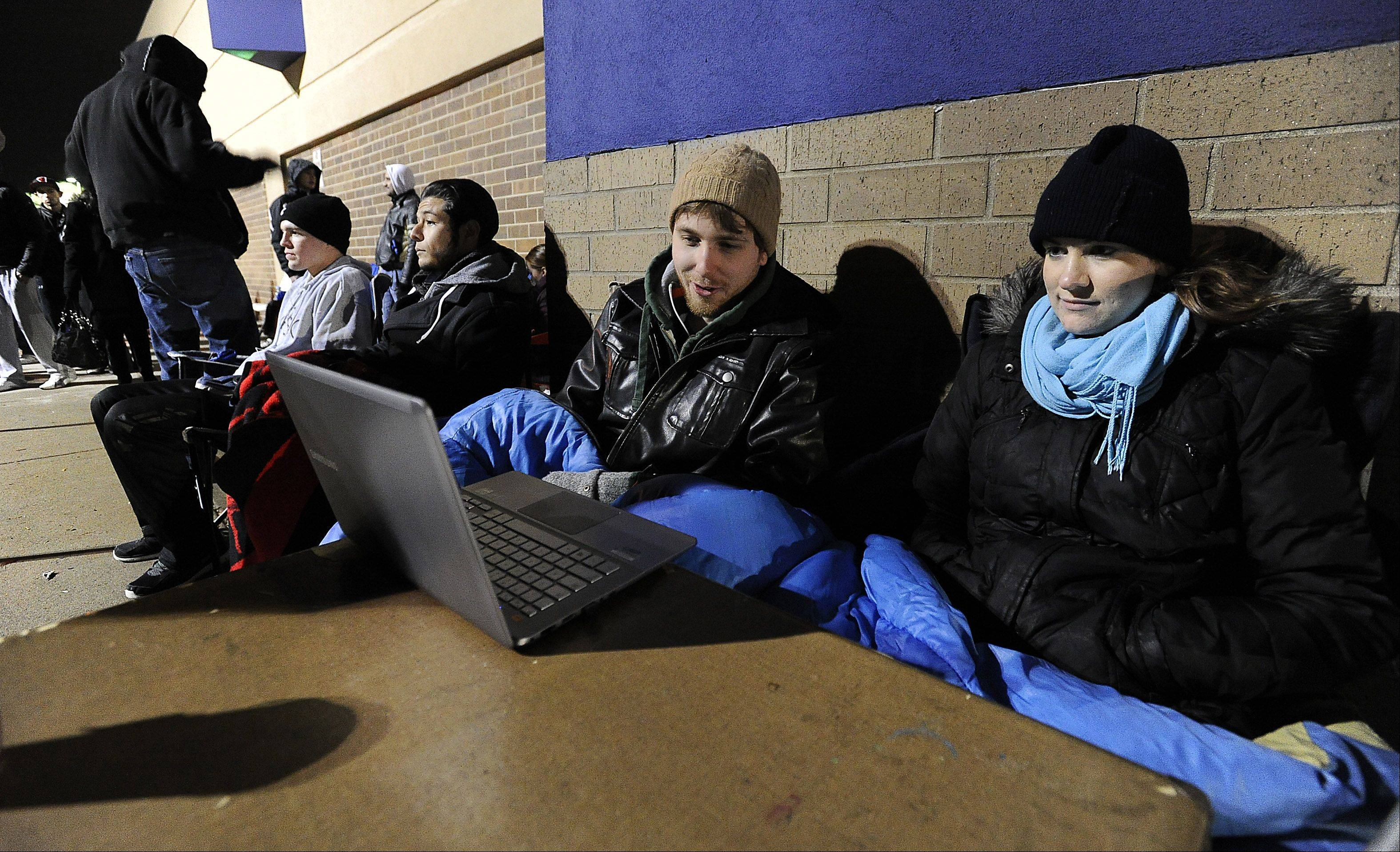 Brian Gates of Arlington Heights and Lauren Gates of Chicago were the first in line camping out at Best Buy in Arlington Heights — starting at noon Thursday — waiting for the new Sony PlayStation 4 to be sold at midnight. To pass the time they watched streaming videos on their computer.
