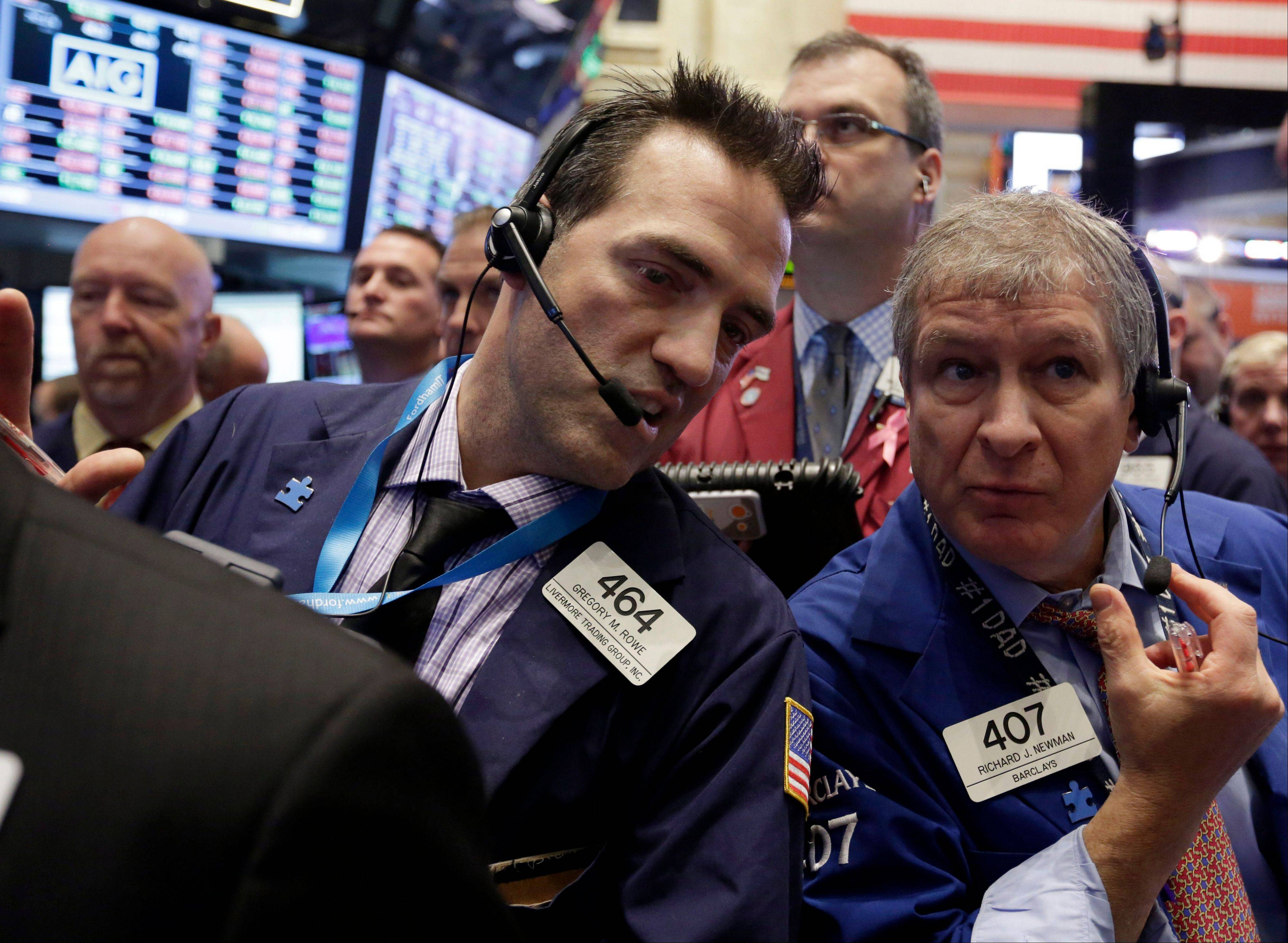 Traders Gregory Rowe, left, and Richard Newman confer on the floor of the New York Stock Exchange. World stock markets bounced higher Thursday after prepared testimony for the confirmation hearing of incoming Federal Reserve chief suggested the U.S. central bank won't reduce its economic stimulus until March next year or later.