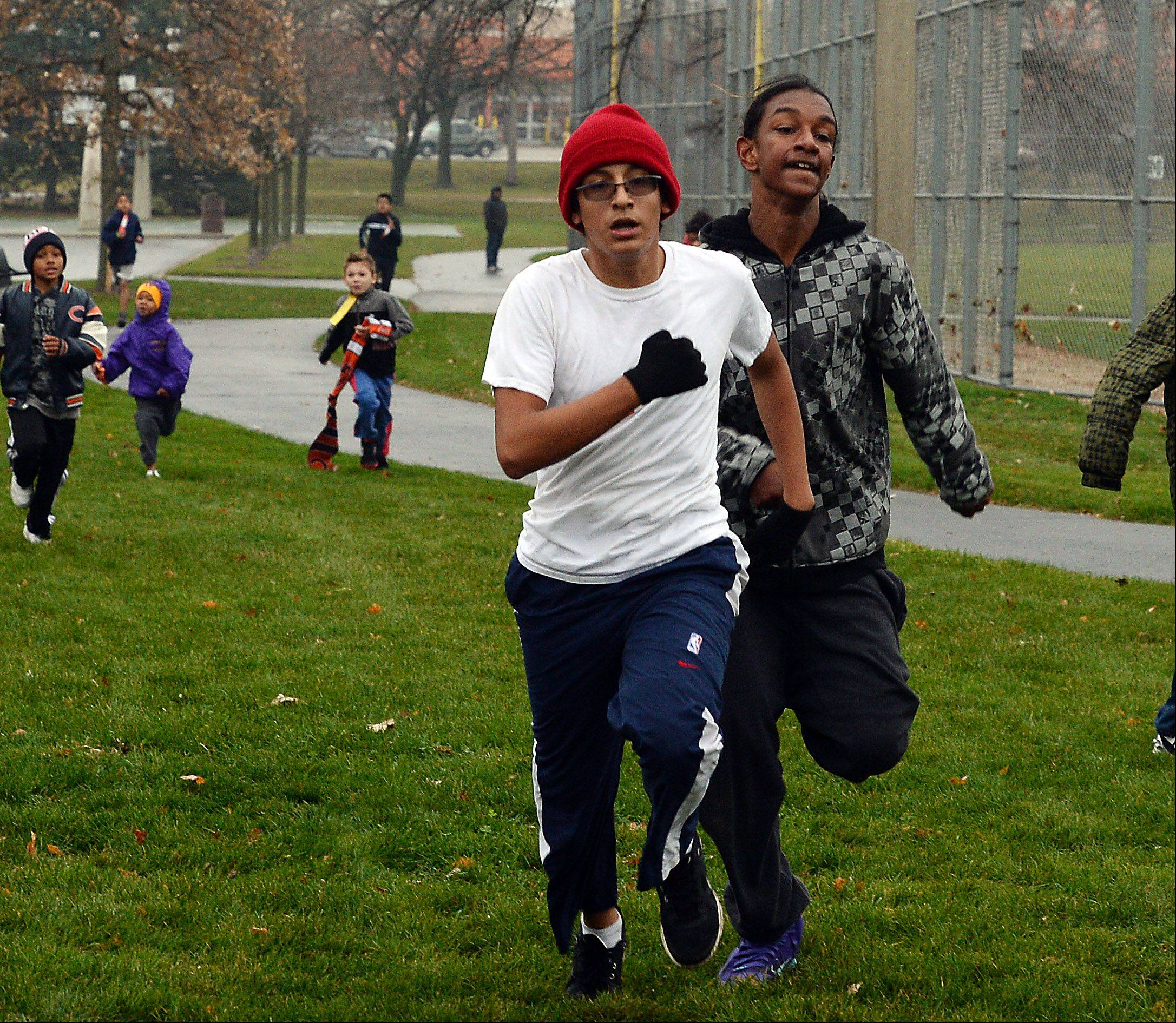In a photo finish, Jose Abonce, 13, left, of Waukegan claims victory over Sincere Geertz, 13, of Waukegan in the 3/8 mile Turkey Trot for their age group at Belvidere Park on Saturday.