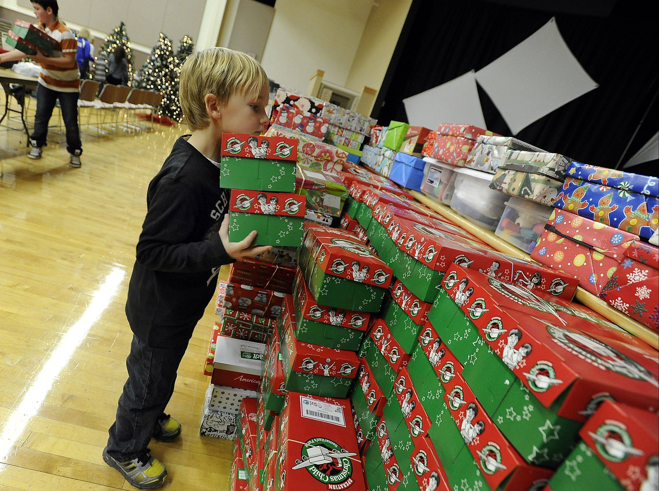 Grayson Peterson, 6, of Wisconsin stacks fully loaded Christmas boxes Saturday during Operation Christmas Child at Immanuel Church in Gurnee. He was helping out his grandfather, Doug Peterson, who is from Libertyville.