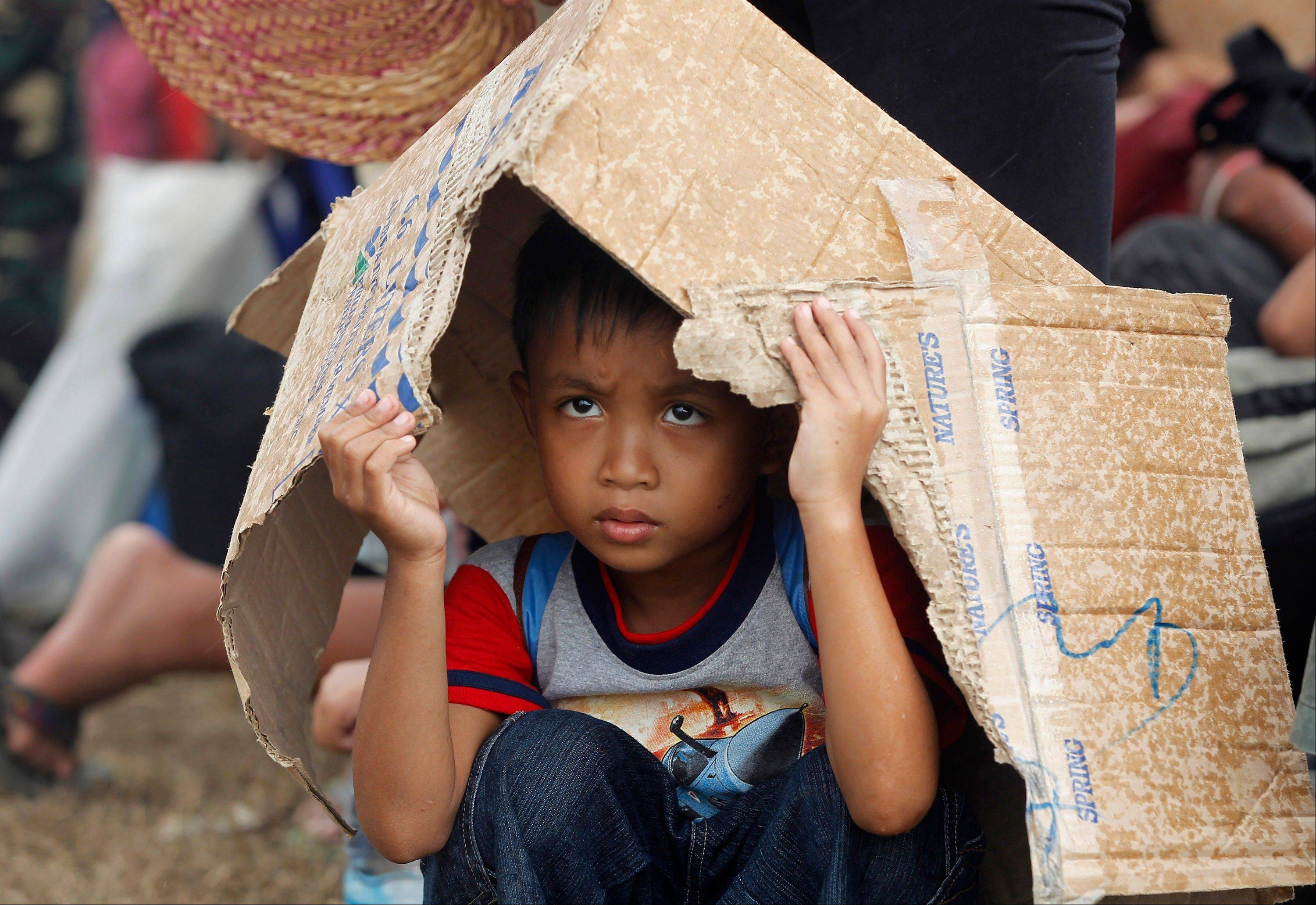 A young boy shields himself from the rain while waiting for an evacuation flight at the airport in Tacloban, central Philippines, Thursday, Nov. 14, 2013.