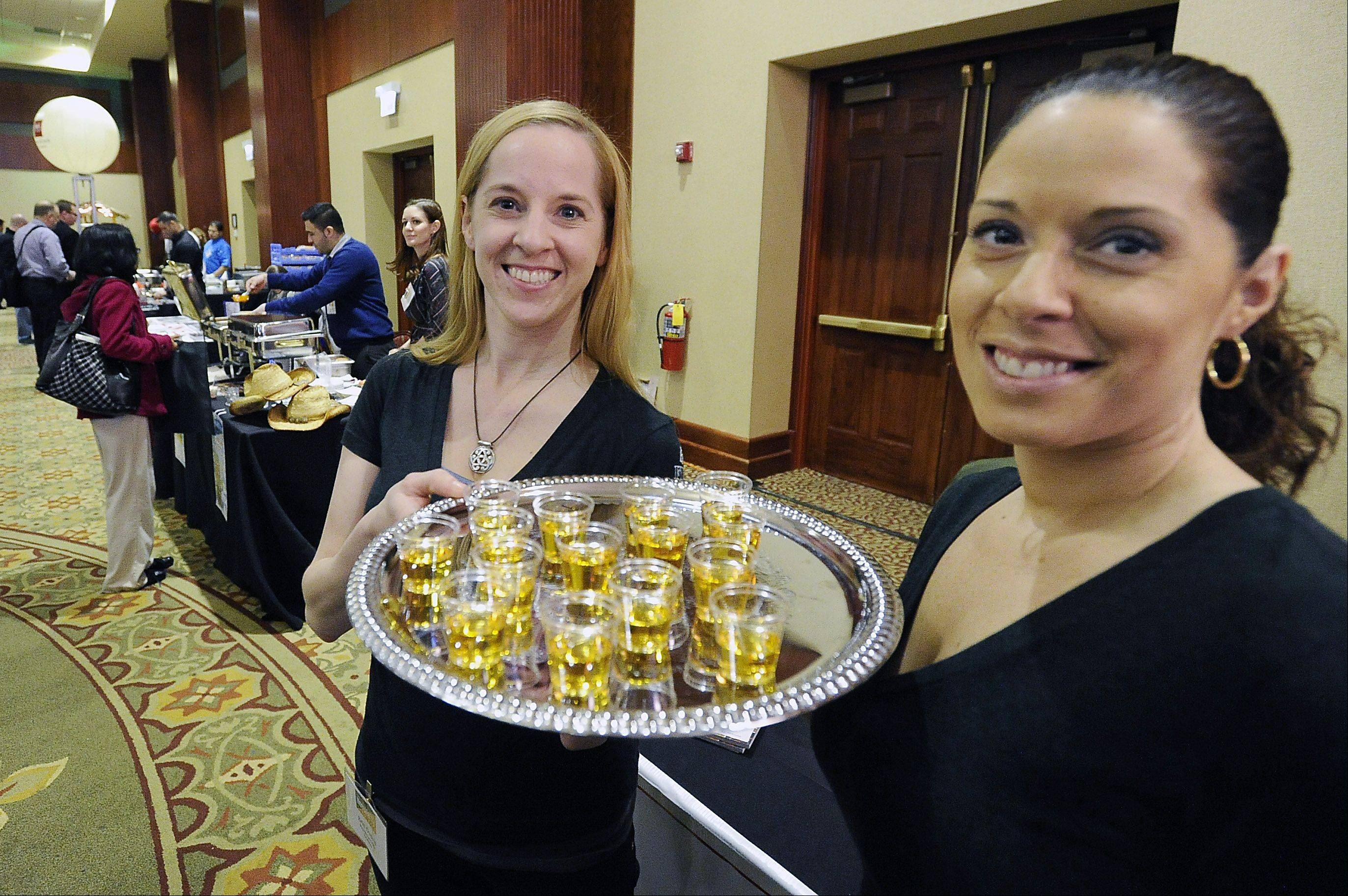 Erin Gussis and Deborah Guerrieri, sales managers at Five Roses Pub of Rosemont, hand out drink samples Thursday at Northwest Hospitality Expo 2013 at the Meadows Club in Rolling Meadows.