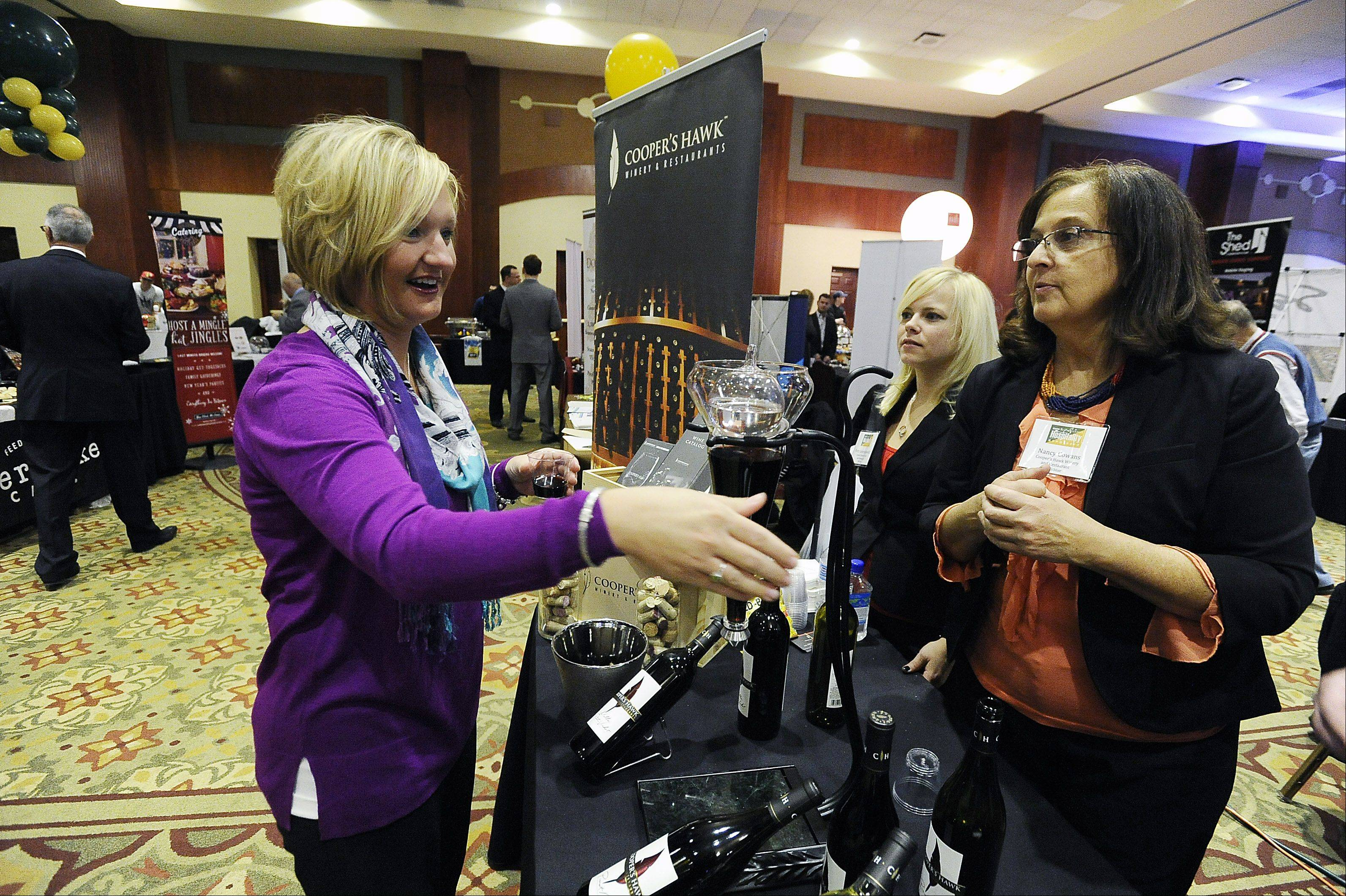 Jackie Jensen of Downers Grove samples wine from Patty Jastrzebowski and Nancy Cowans of Cooper's Hawk in Arlington Heights at Northwest Hospitality Expo 2013 at the Meadows Club in Rolling Meadows.