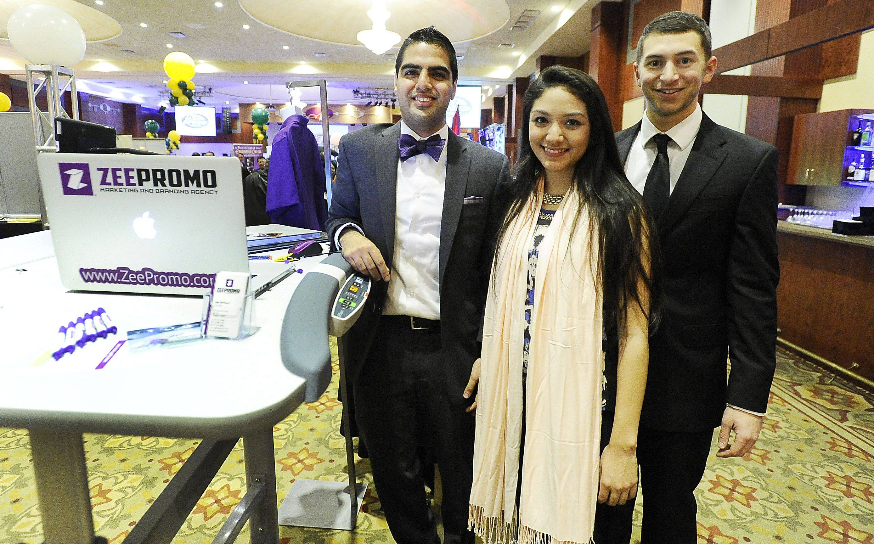 Zee Bhimani, a consultant, along with Betzabel Mendez and Daniel Pessah of ZeePromo Marketing and Branding Agency of Chicago, show off their products Thursday at Northwest Hospitality Expo 2013 at the Meadows Club in Rolling Meadows.