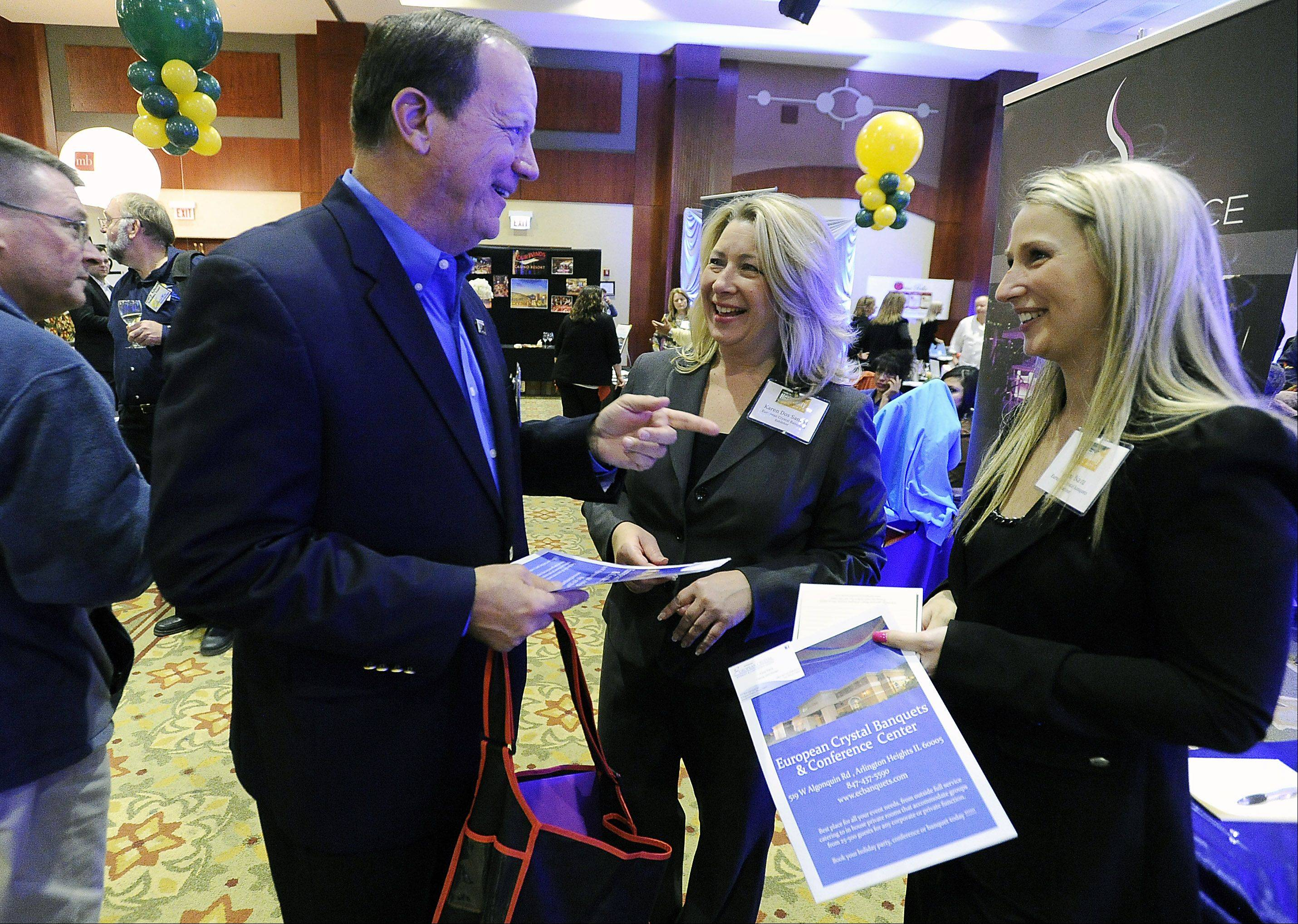Karen Dos Santos, sales associate, and Anna Nava, catering sales manager of European Crystal of Arlington Heights talk Thursday with Wayne Oates, a senior marketing coach of Elk Grove, at Northwest Hospitality Expo 2013 at the Meadows Club in Rolling Meadows.