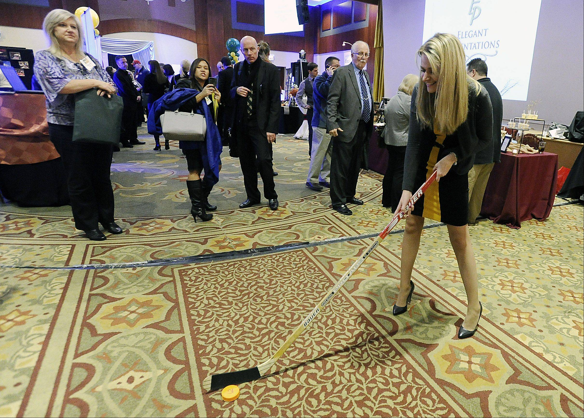 Taking a swing at a hockey puck as part of a promo for Wolves Hockey is Katie Teele of Chicago at Thursday's Northwest Hospitality Expo 2013 at the Meadows Club in Rolling Meadows.