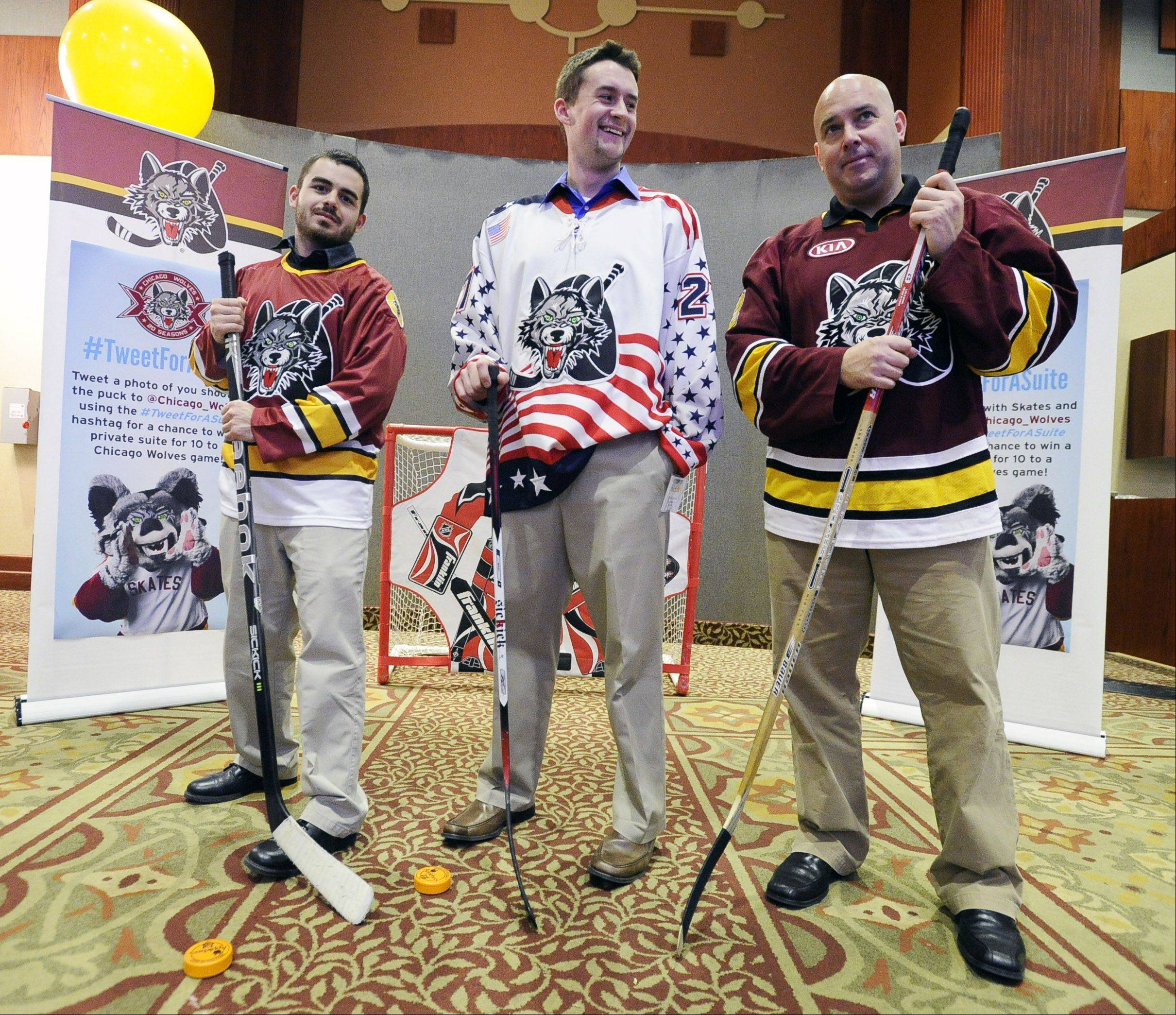 Ricky Campione and Mike Czopek, both sales representatives from the Chicago Wolves, and Dave Pawelek, senior director of strategic alliances, show off their hockey skills Thursday at Northwest Hospitality Expo 2013 at the Meadows Club in Rolling Meadows.