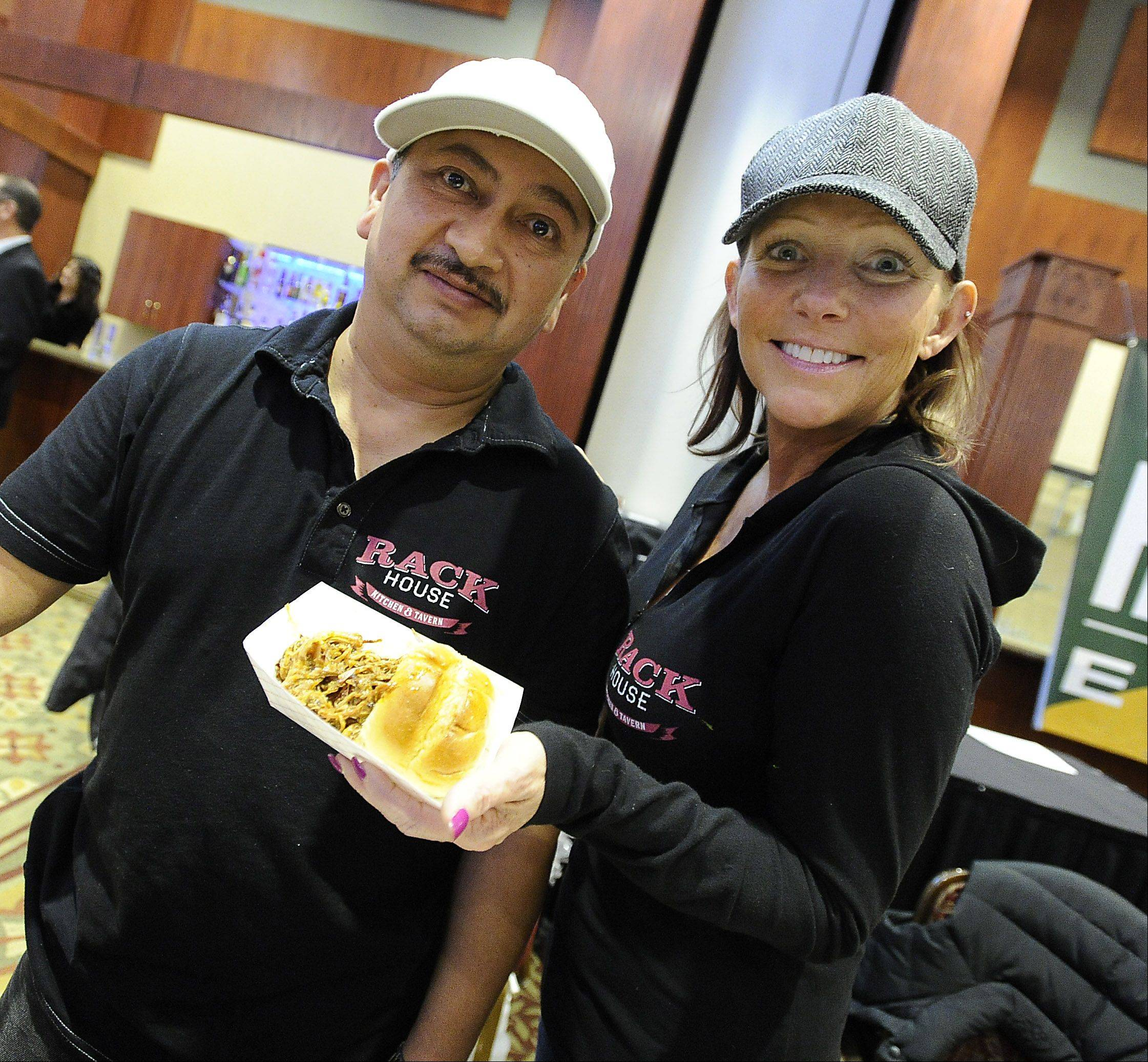 Manager Tracy Hernandez and chef Nicolas Pastrani from the Rack House of Arlington Heights serve up pulled pork Thursday at Northwest Hospitality Expo 2013 at the Meadows Club in Rolling Meadows.