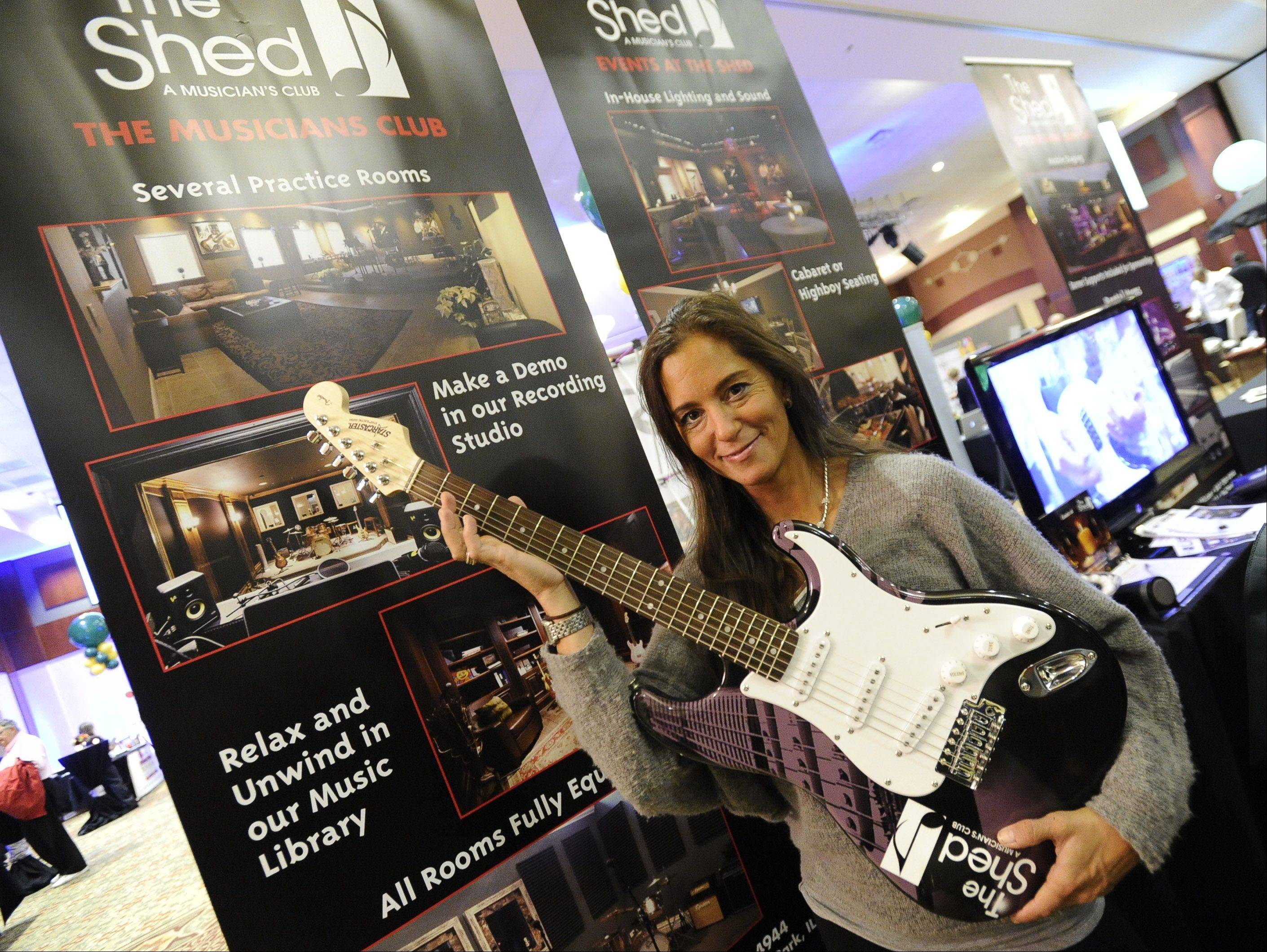Kimberly Schiffman, vice-president of sales and events at The Shed, A Musicians's Club in Highland Park, gets rocking Thursday at Northwest Hospitality Expo 2013 at the Meadows Club in Rolling Meadows.