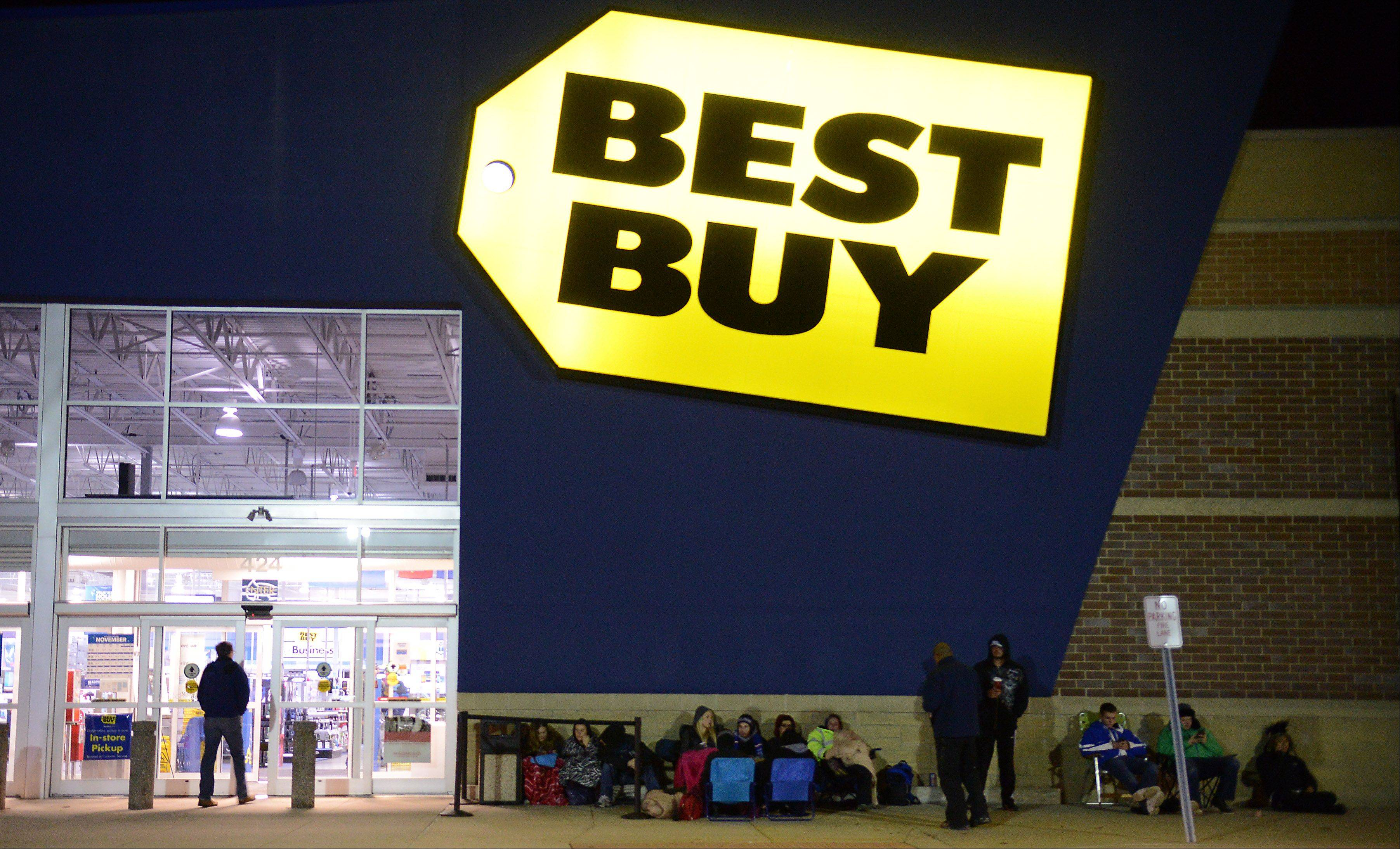 Rick West/rwest@dailyherald.comAbout 15 people wait outside the South Elgin Best Buy Thursday night to be among the first to buy the new Playstation 4 being released at midnight. The first people in line got there at 11:30 am.