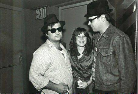 "After the success of ""National Lampoon's Animal House,"" John Belushi, left, starred with friend Dan Aykroyd, right, in the equally popular ""Blues Brothers"" movie. Belushi's widow, Judy Jacklin Belushi Pisano, center, is working with executive producer Aykroyd on a new biopic film starring Emile Hirsch as her late husband."