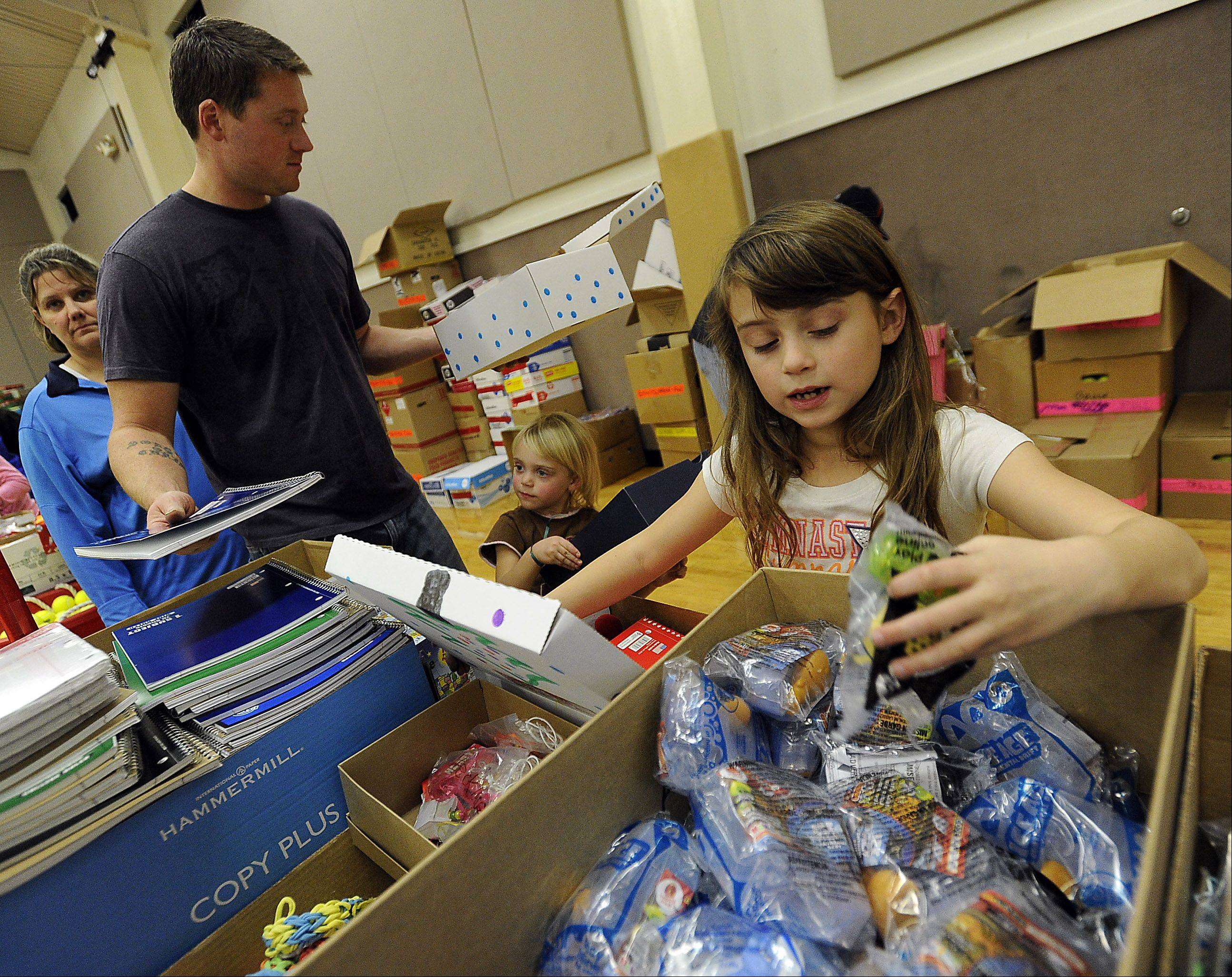 Raegan Hawn, 7, picks outs toys for her Christmas box at Operation Christmas Child with her dad, Nick, and sister, Sydney, 4, of Grayslake at Immanuel Church in Gurnee on Saturday. The boxes will be shipped to places like Kenya, Zambia, India and Madagascar.