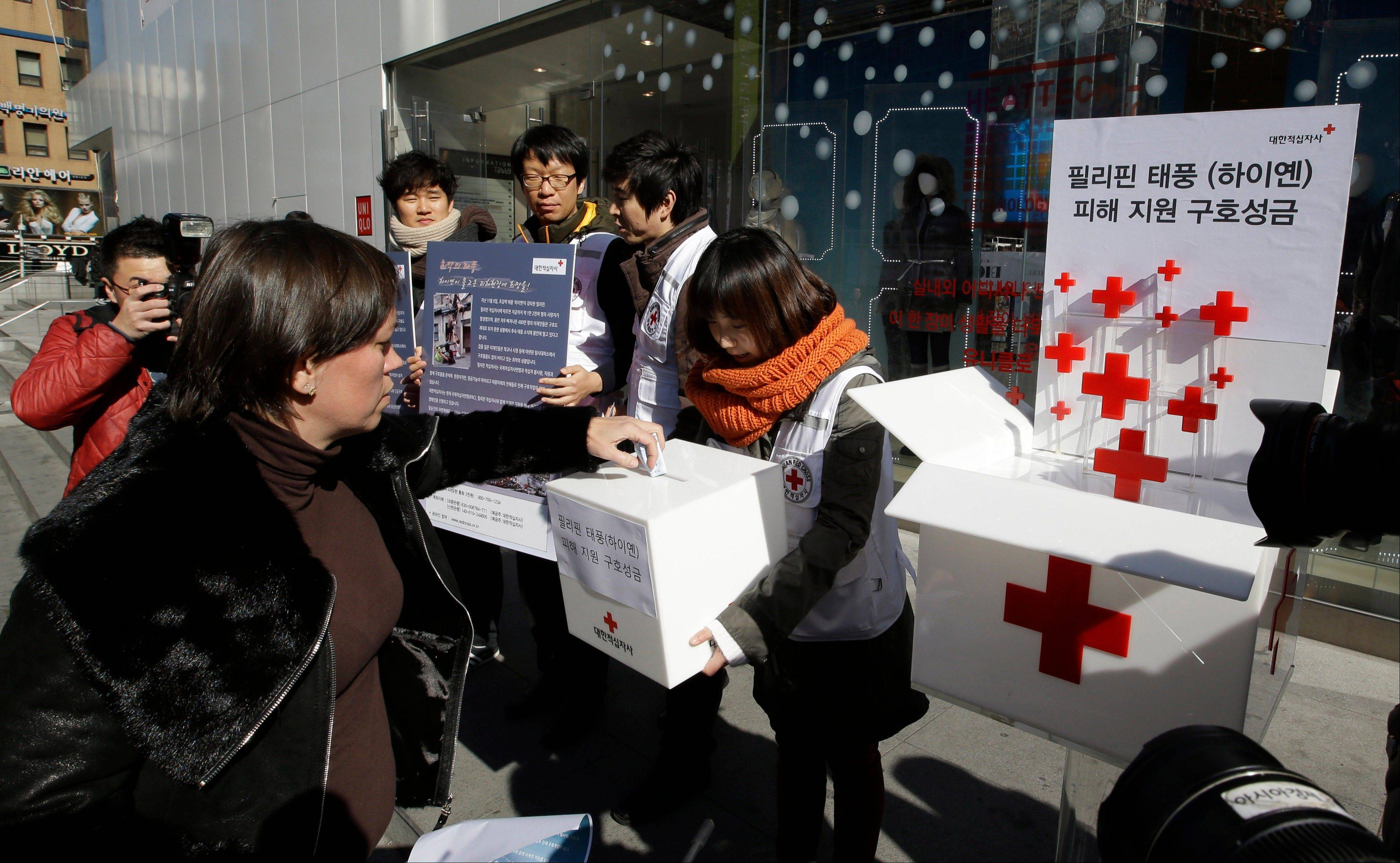 "A tourist donates money for the victims of Typhoon Haiyan in the Philippines during a fundraising campaign on a street in Seoul, South Korea. Signs read, ""Aid donation for the victims of Typhoon Haiyan."""