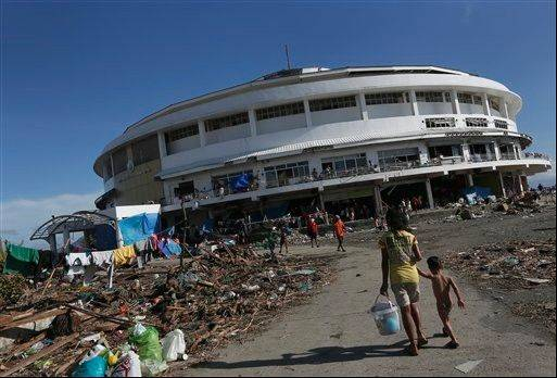 A young girl walks her brother to the Tacloban City Convention Center known as the Astrodome Thursday, Nov. 14, 2013, where hundreds of displaced typhoon survivors have set up makeshift shelters throughout the complex's once bustling shops and popular basketball court.