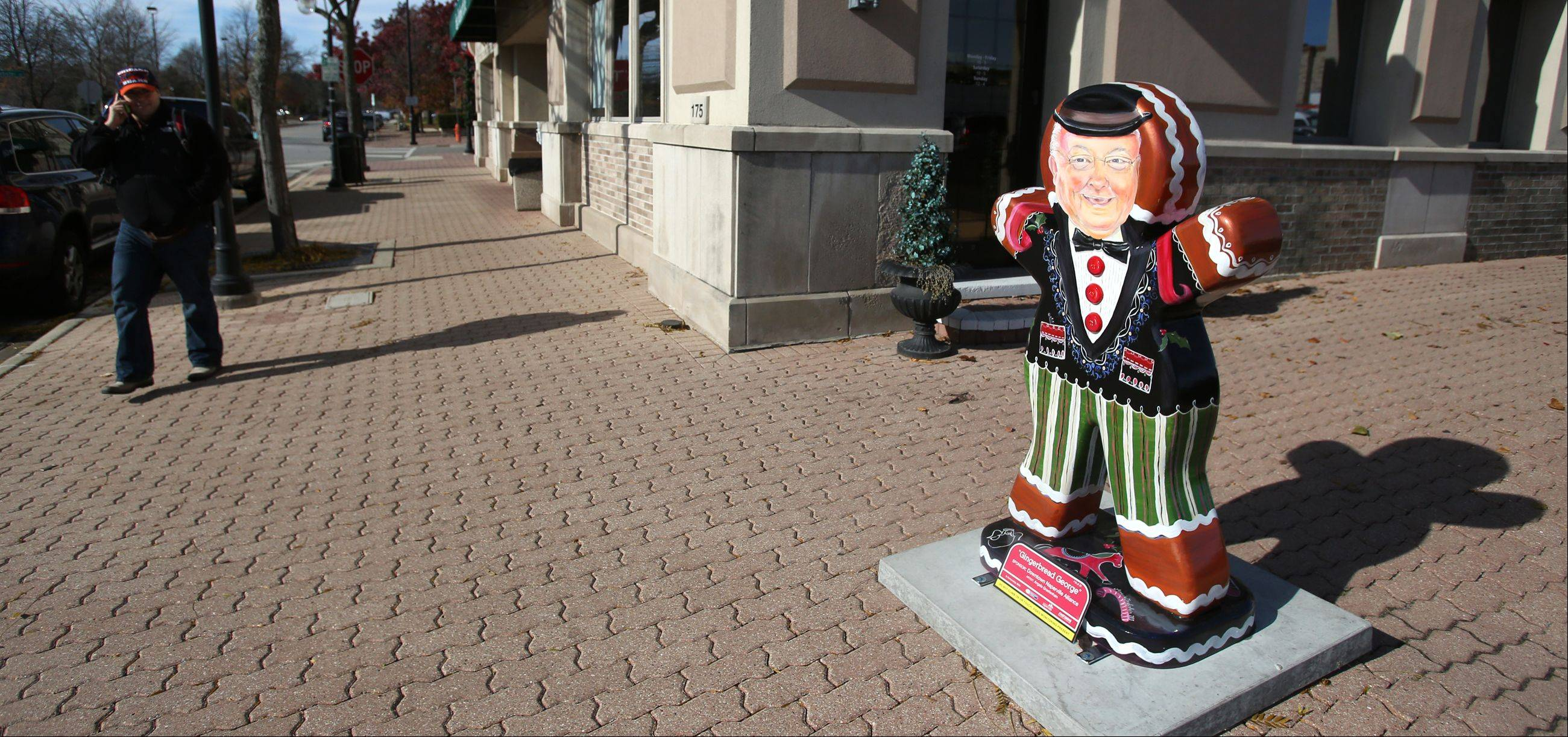 """Gingerbread George,"" a sculpture painted to look like Naperville Mayor George Pradel, rests on a downtown Jackson Avenue corner, where it is one of 25 gingerbread sculptures that will be on display throughout the holiday season. Businesses have sponsored the sculptures, painted by local artists or students, through a Downtown Naperville Alliance holiday art program."