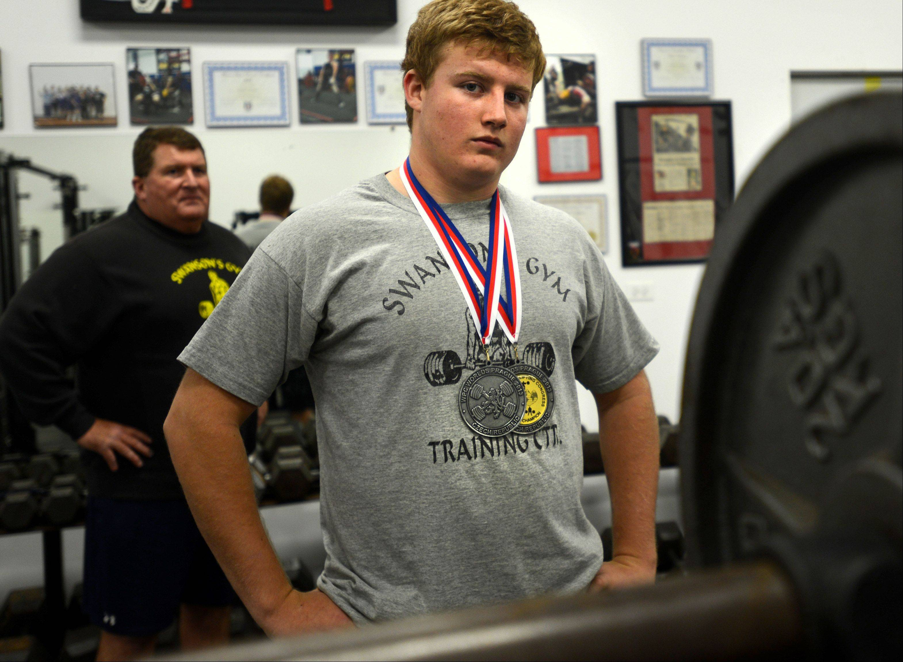 Dominic Swanson, a Huntley High School sophomore, just became the holder of five world weightlifting records. Dad Gary, a former powerlifter himself, is the family trainer.