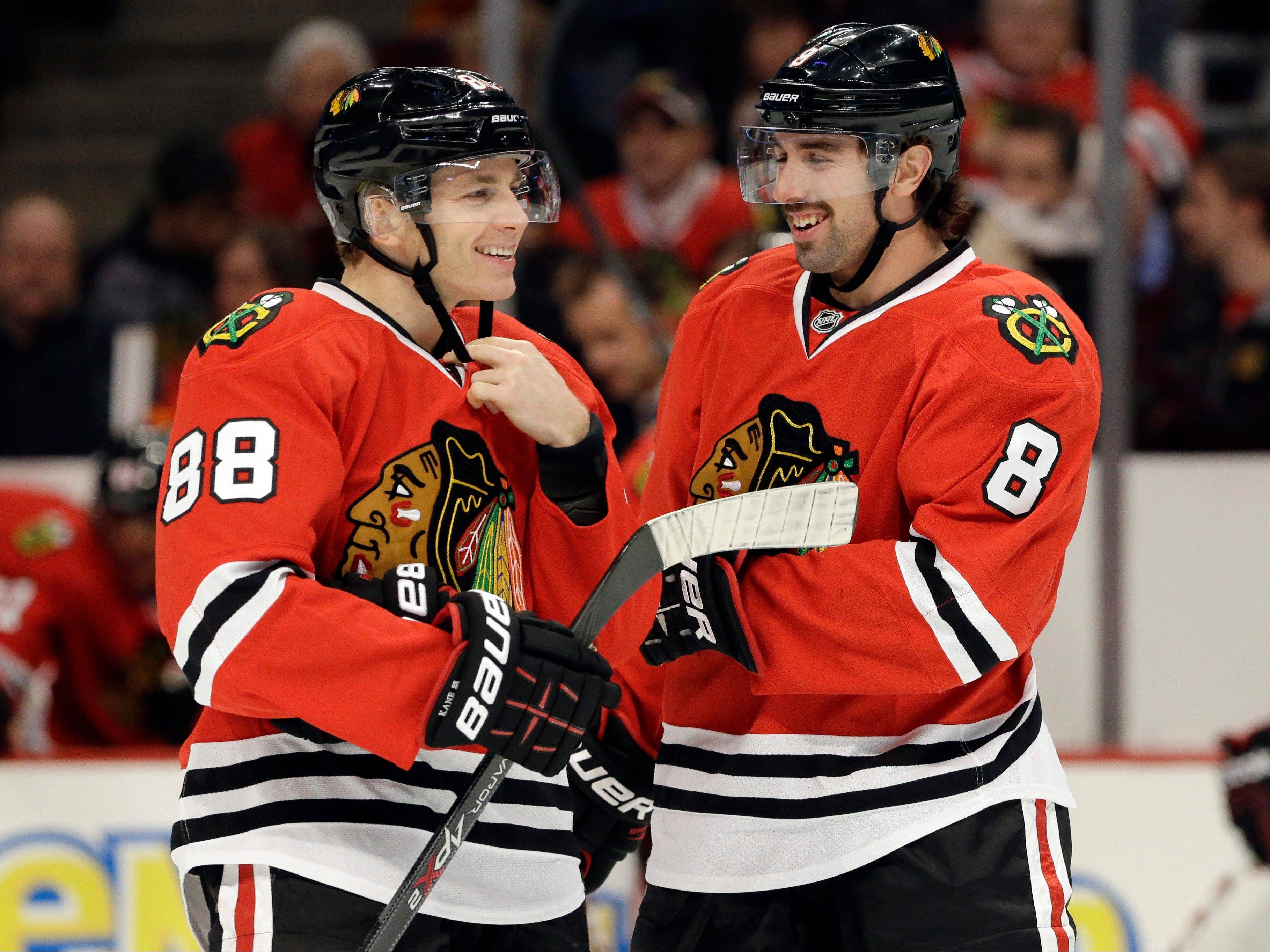Chicago Blackhawks' Patrick Kane, left, smiles as he talks with Nick Leddy (8) during the first period of an NHL hockey game against the Phoenix Coyotes in Chicago, Thursday, Nov. 14, 2013.