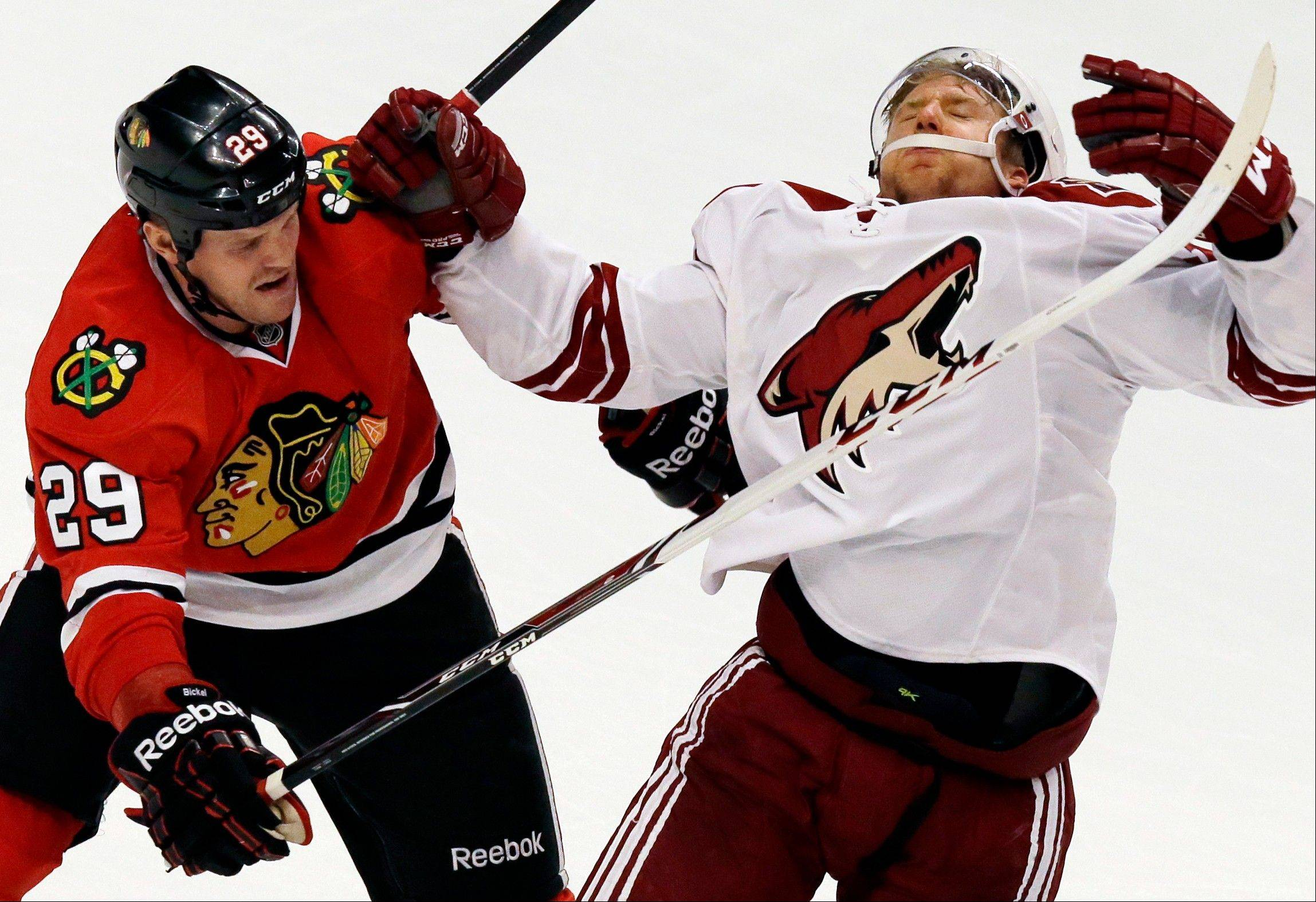 Phoenix Coyotes' Rob Klinkhammer, right, is hit by the Blackhawks' Bryan Bickell during the third period of an NHL hockey game in Chicago, Thursday, Nov. 14, 2013. The Blackhawks won 5-4.