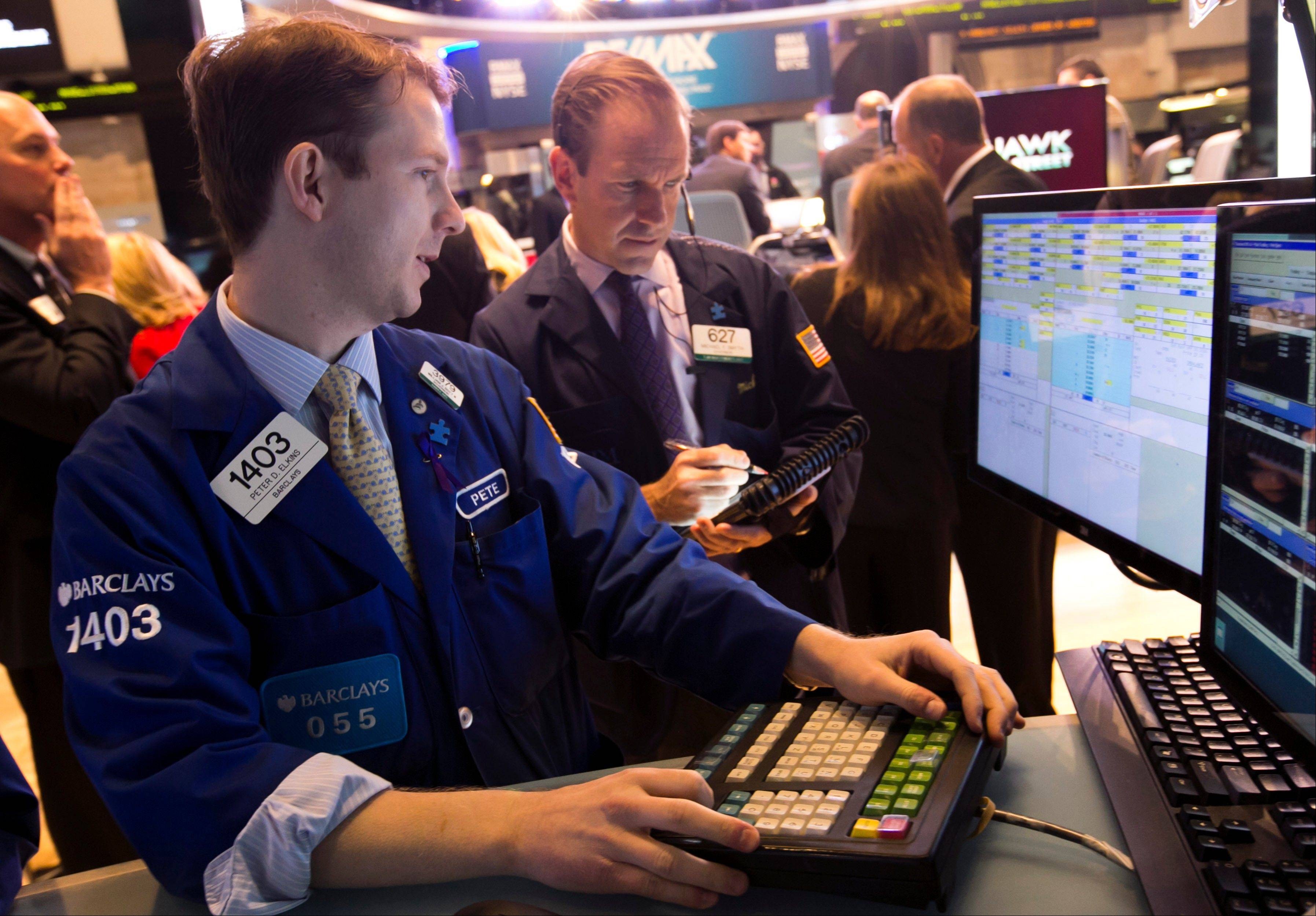 Specialist Peter Elkins, left, and trader Michael Smyth work Tuesday on the floor of the New York Stock Exchange.