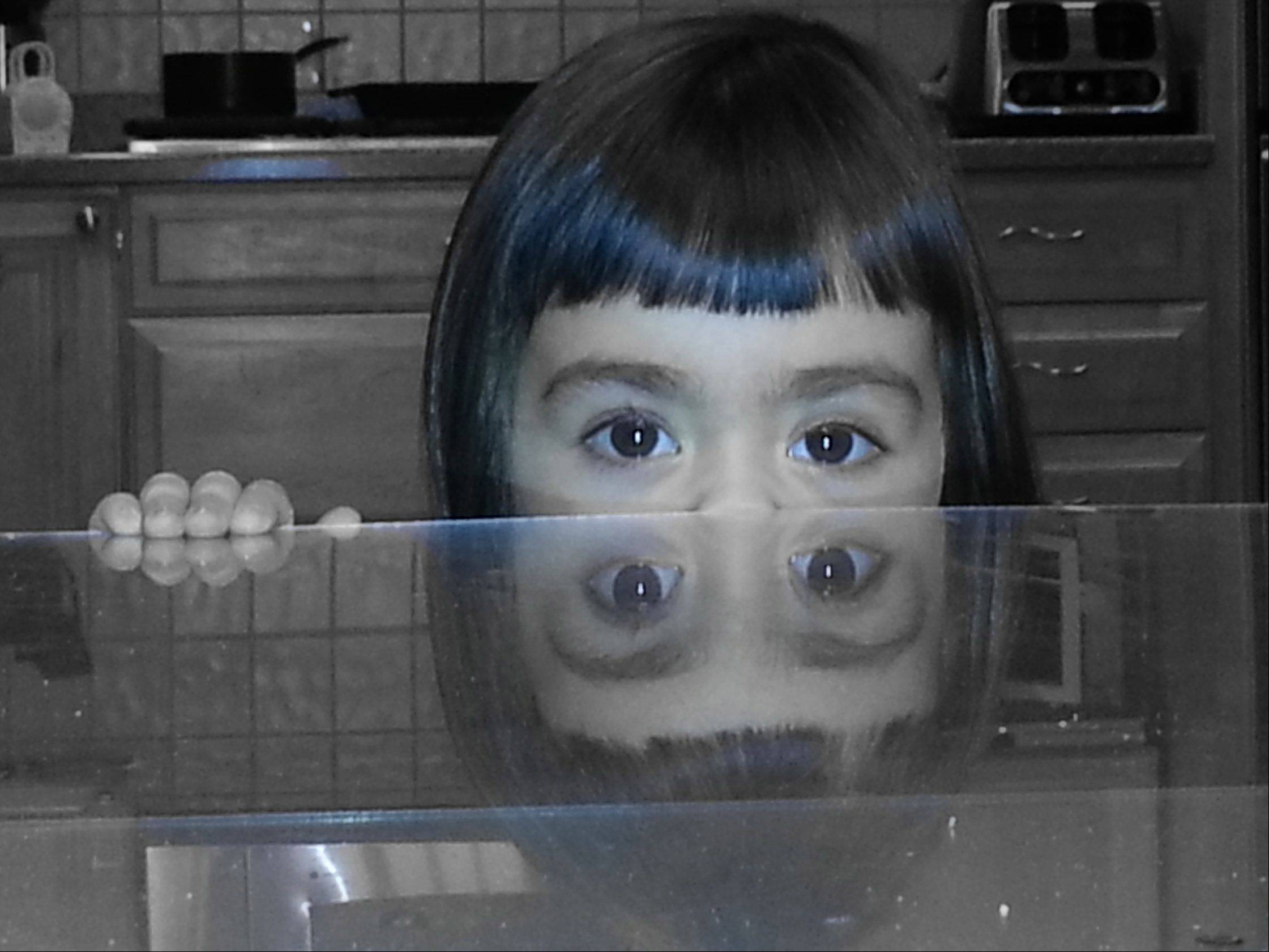 A young girl stares over the kitchen table with a reflective surface waiting to strike at any moment.