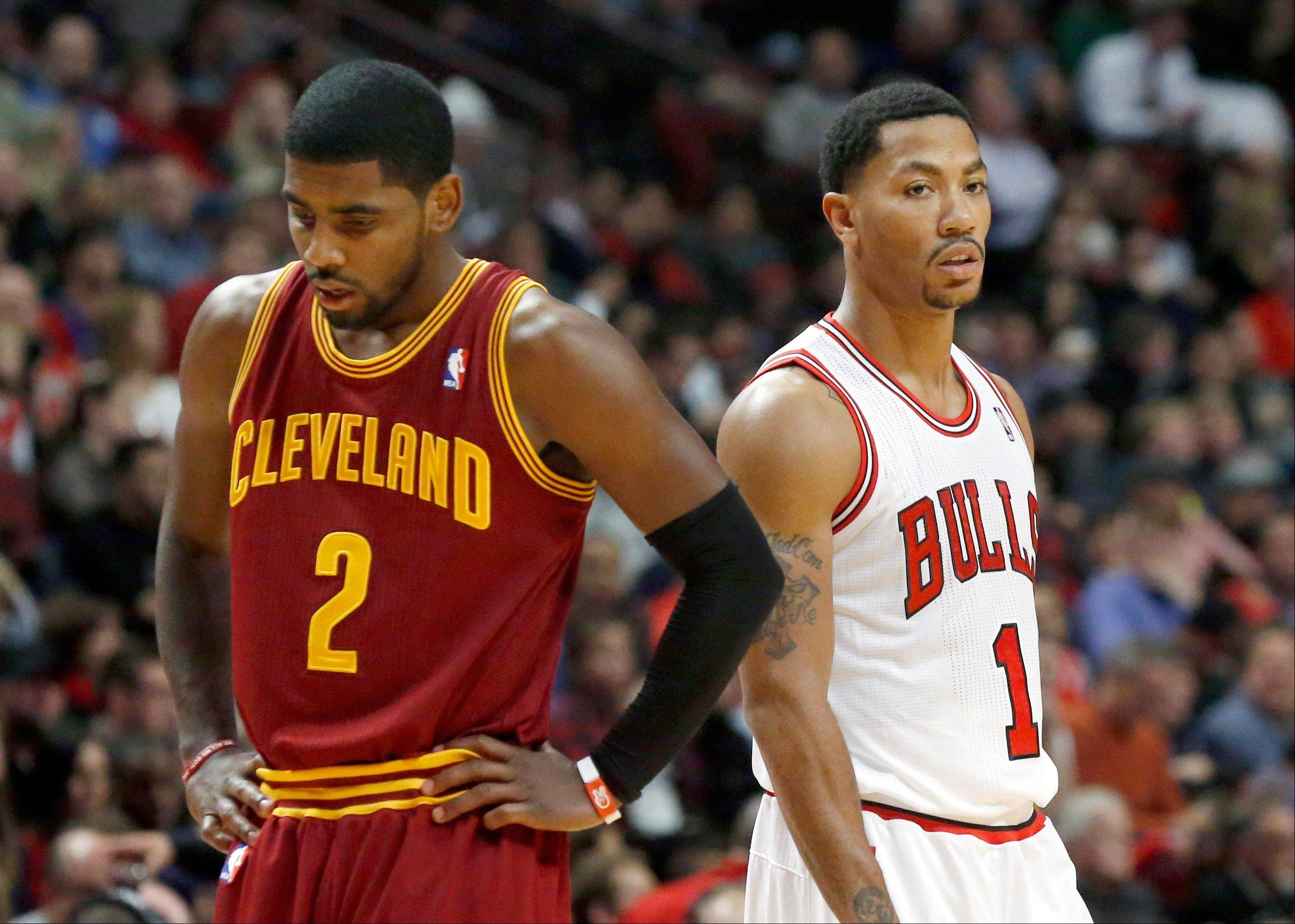 Chicago Bulls point guard Derrick Rose (1) and Cleveland Cavaliers point guard Kyrie Irving wait for a Bulls free throw attempt during the second half of an NBA basketball game against the Chicago Bulls Monday, Nov. 11, 2013, in Chicago. The Bulls won 96-81. (AP Photo/Charles Rex Arbogast)