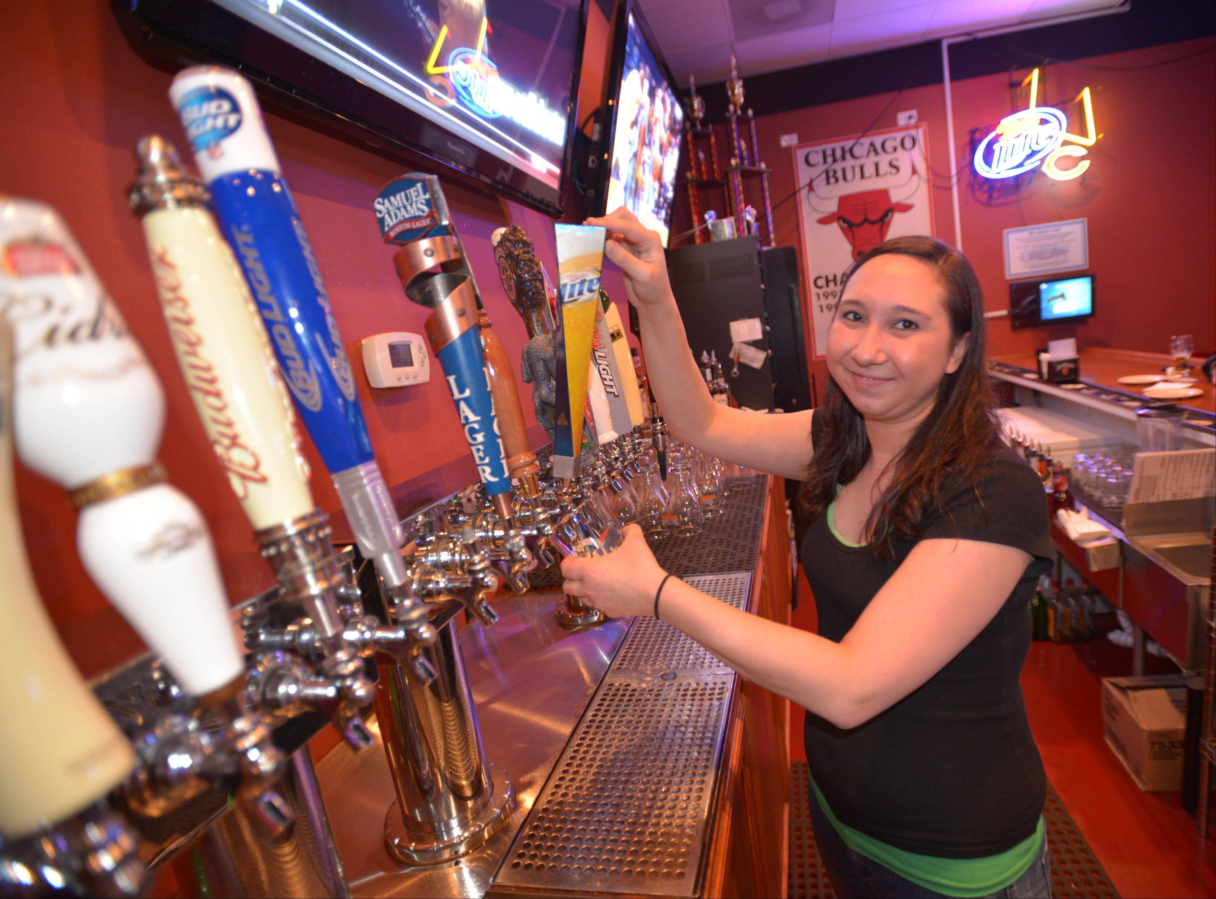 Tricia Ortolano taps a beer at The Town Bar & Grill in Aurora.