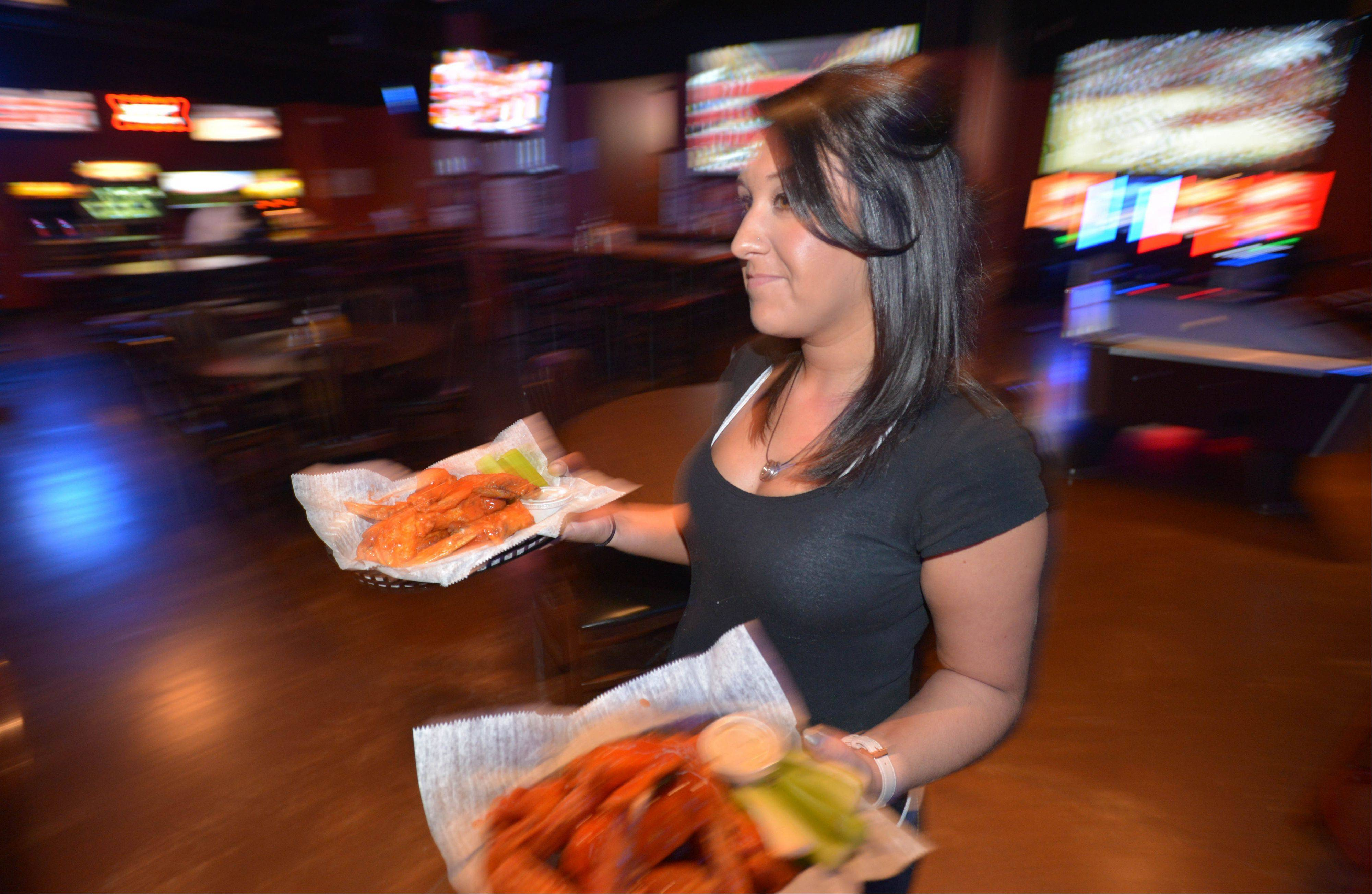 Server Taylor Hatcher brings some hot wings to a table at The Town Bar & Grill in Aurora.