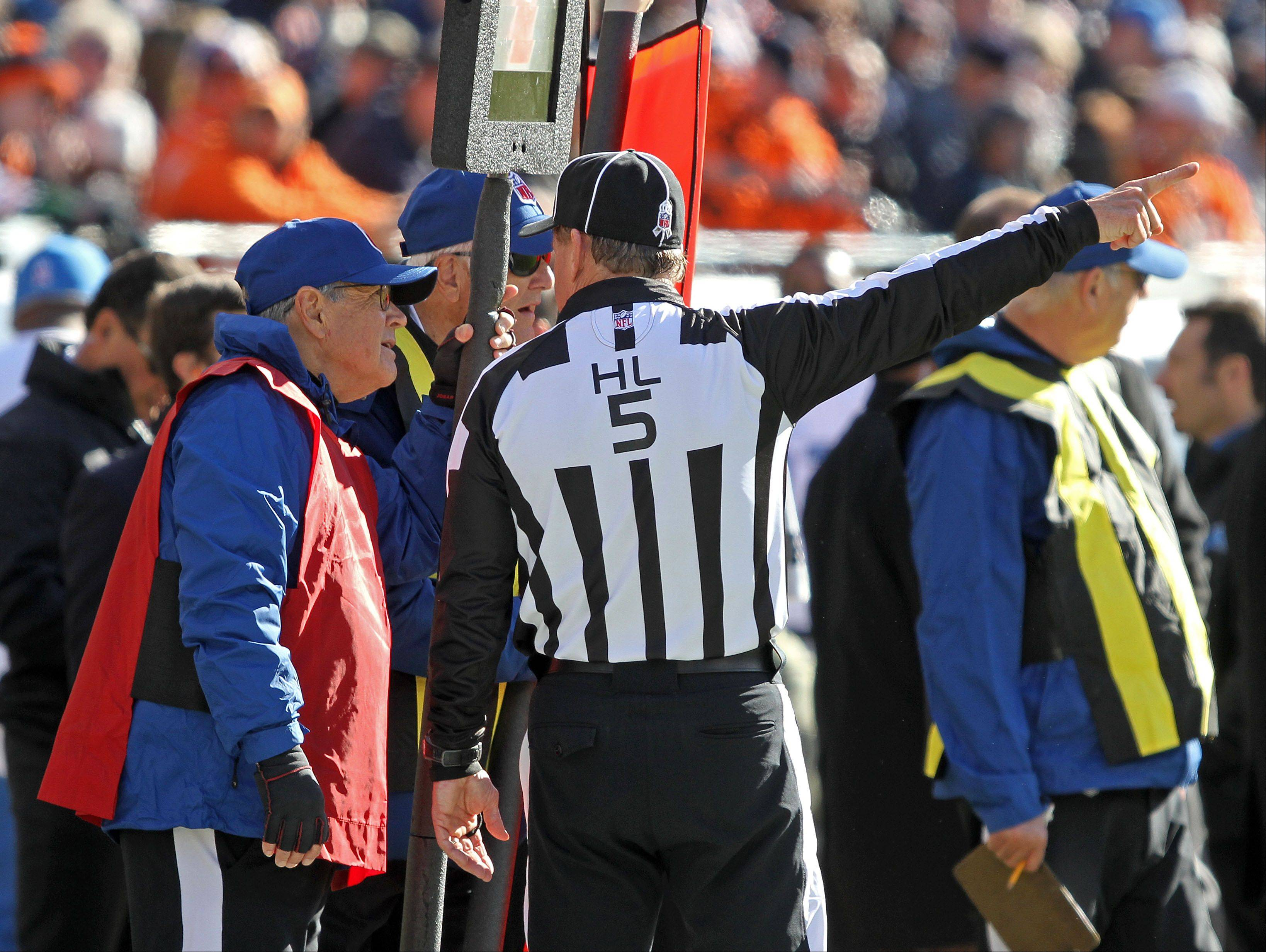 Harold Schwind of Roselle listens to instructions from NFL Head Linesman John McGrath while working the down box during the Bears game Sunday, Nov. 9.