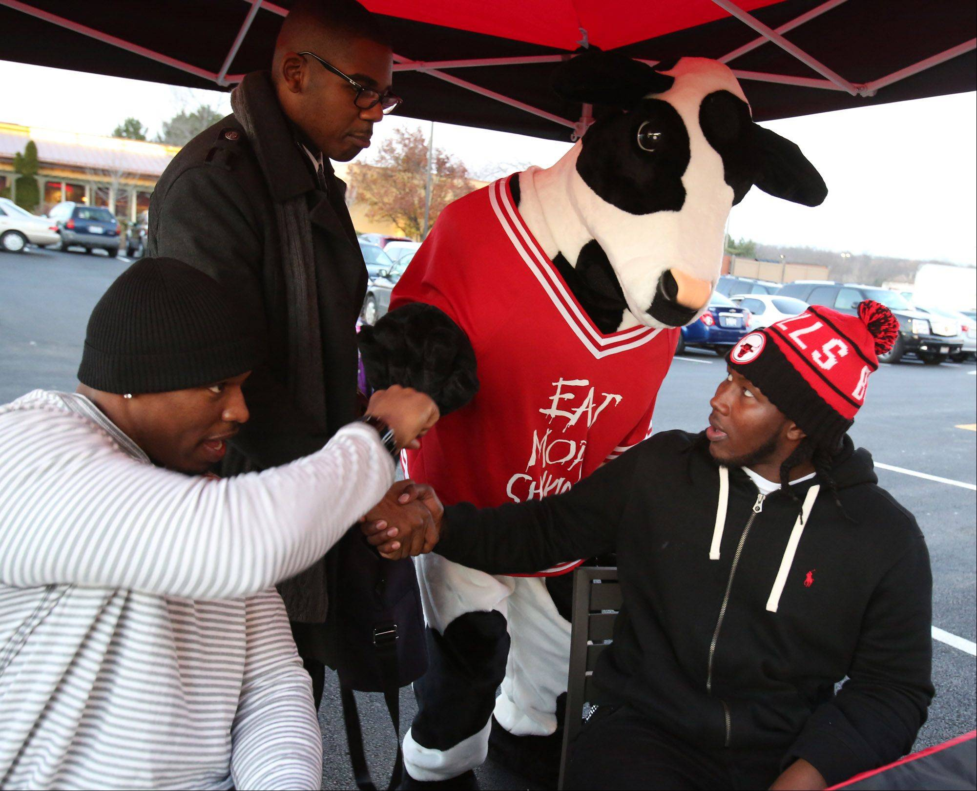 Chicago Bears linebacker Khaseem Greene, right, gets a knuckles bump from Brandon Hurst of Chick-fil-A Inc. while practice squad tight end Fendi Onobun gets a knuckles bump from a Chick-fil-A cow while signing autographs outside of the new Vernon Hills restaurant Friday.