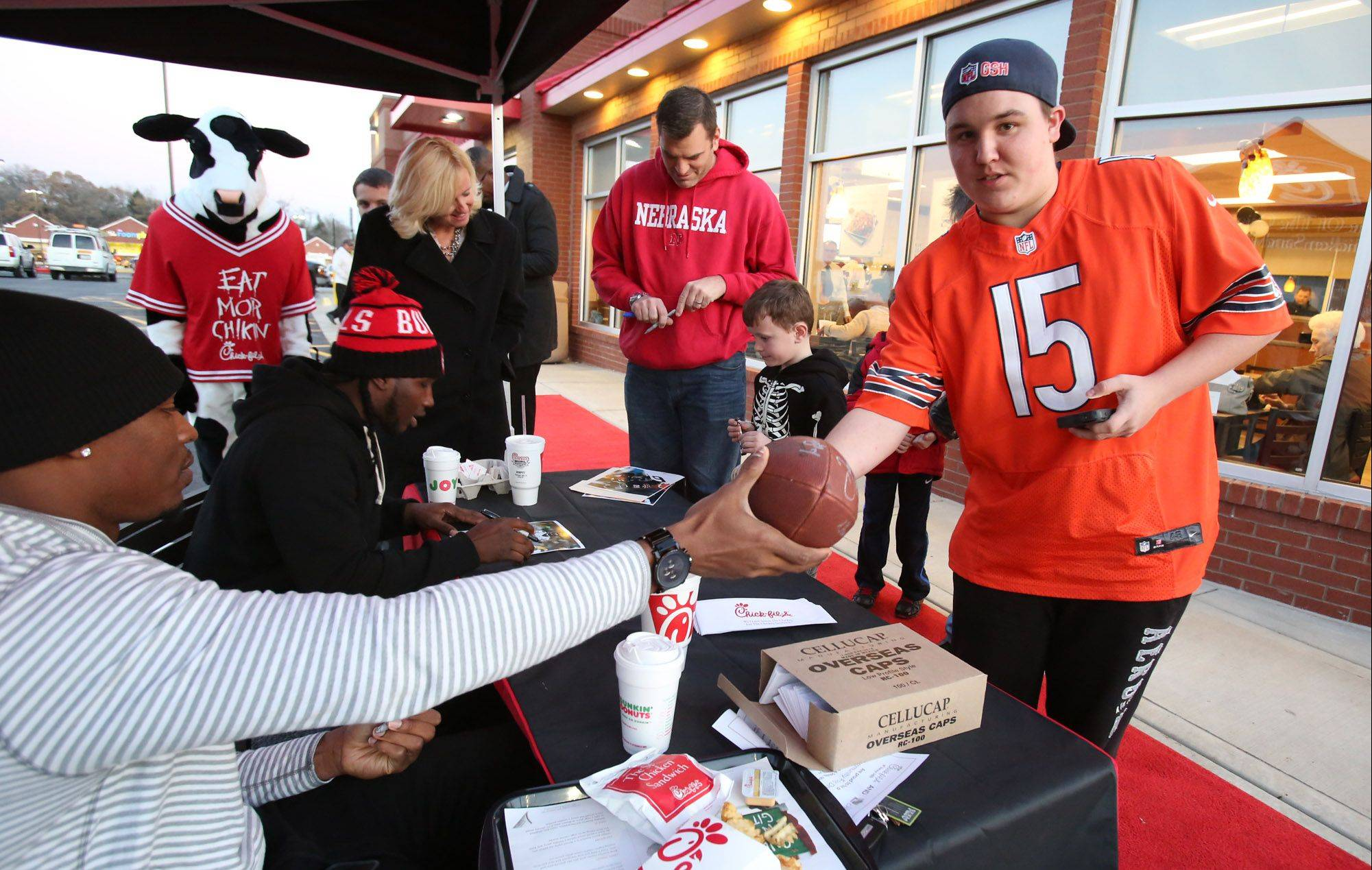 Onobun hands an autographed football to Jake Sellner, 17, of Barrington, after Onobun and Greene, background left, signed the ball.