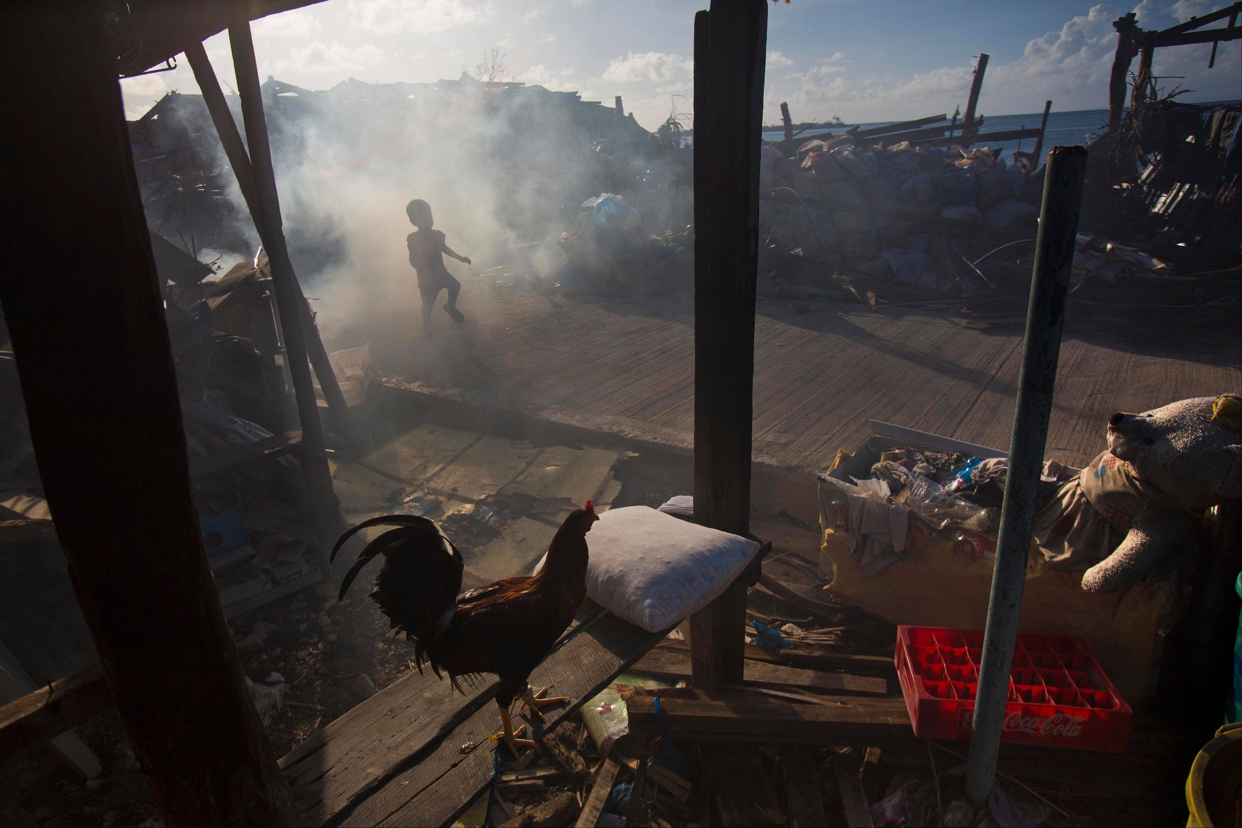 A boy runs through the smoke of a cooking fire in the typhoon-shattered town of Guiuan, Philippines, on Friday, Nov. 15, 2013. Typhoon Haiyan, one of the most powerful storms on record, hit the country's eastern seaboard Nov. 8, leaving a wide swath of destruction.