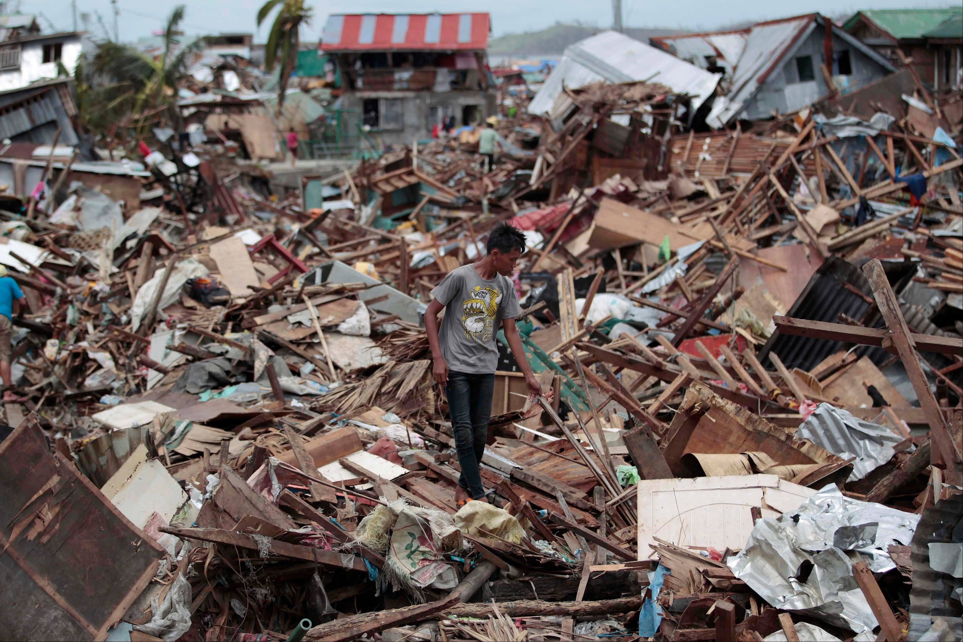 A Filipino man walks among debris from damaged homes at typhoon-hit Tacloban city, Leyte province, central Philippines on Wednesday, Nov. 13, 2013. Typhoon Haiyan, one of the strongest storms on record, slammed into six central Philippine islands on Friday leaving a wide swath of destruction.