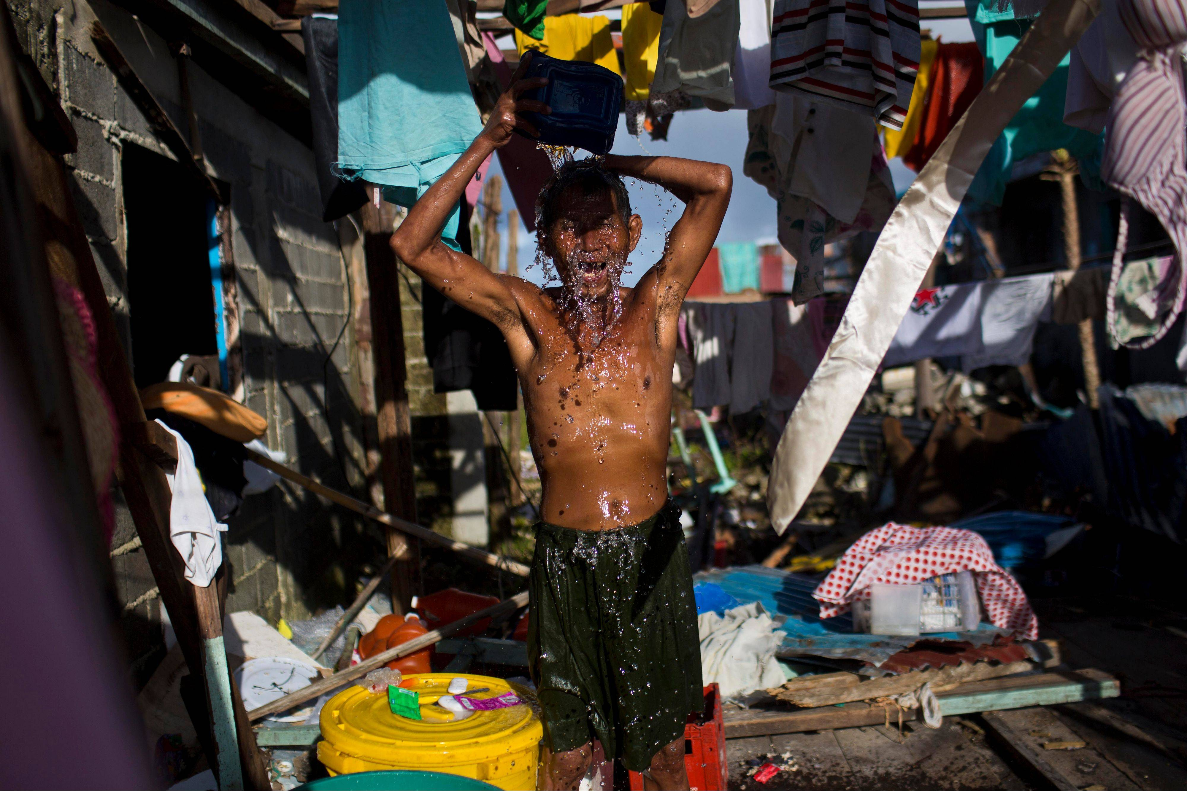 A Typhoon Haiyan survivor bathes in the ruins of his home in Guiuan, Philippines on Friday, Nov. 15, 2013. Typhoon Haiyan, one of the most powerful storms on record, hit the country's eastern seaboard Nov. 8, leaving a wide swath of destruction.