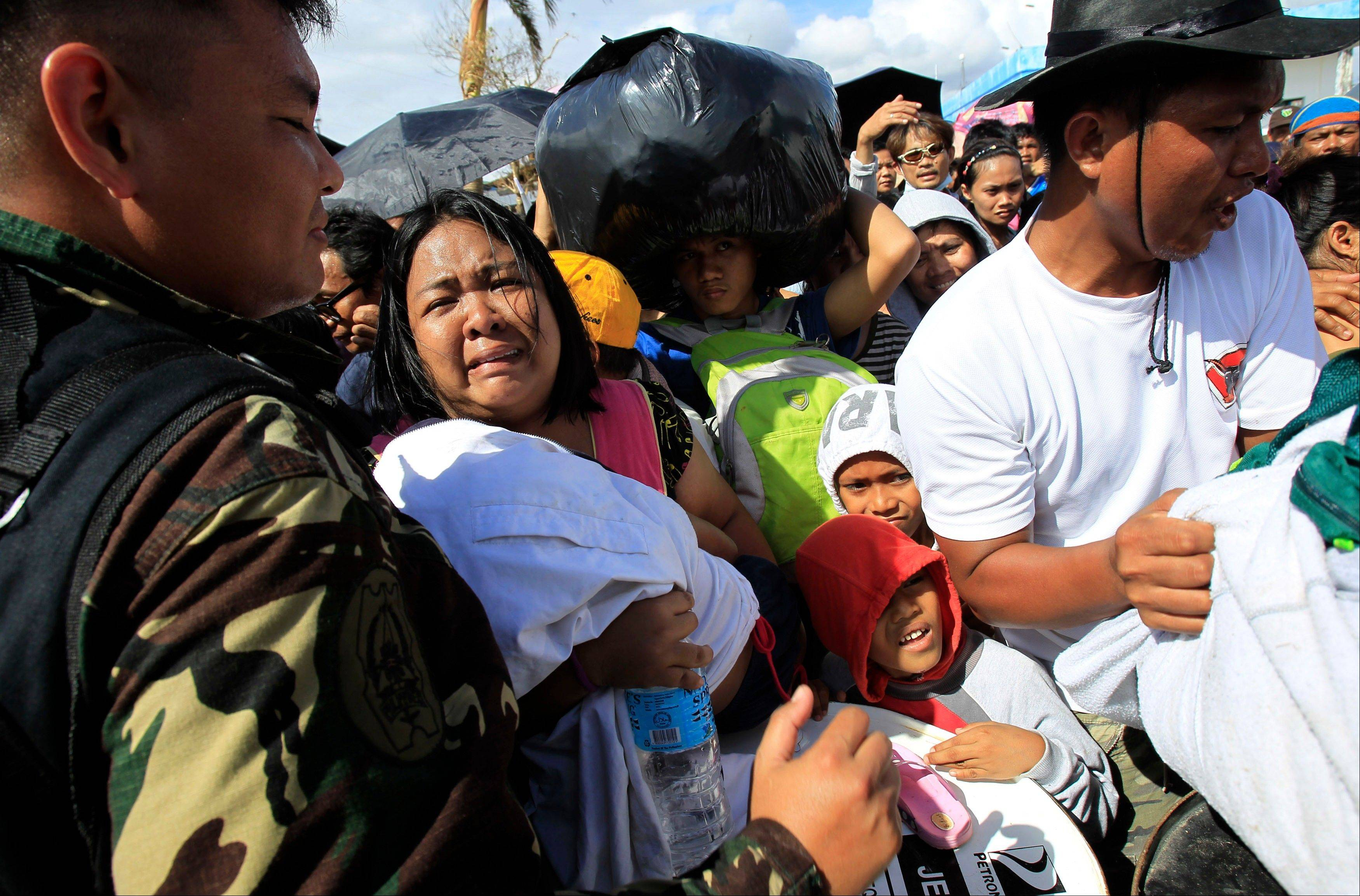 A woman and her child plead from the frantic crowd to be prioritized on an evacuation flight in Tacloban, central Philippines, Thursday, Nov. 14, 2013. Typhoon Haiyan, one of the most powerful storms on record, hit the country's eastern seaboard on Friday, destroying tens of thousands of buildings and displacing hundreds of thousands of people.