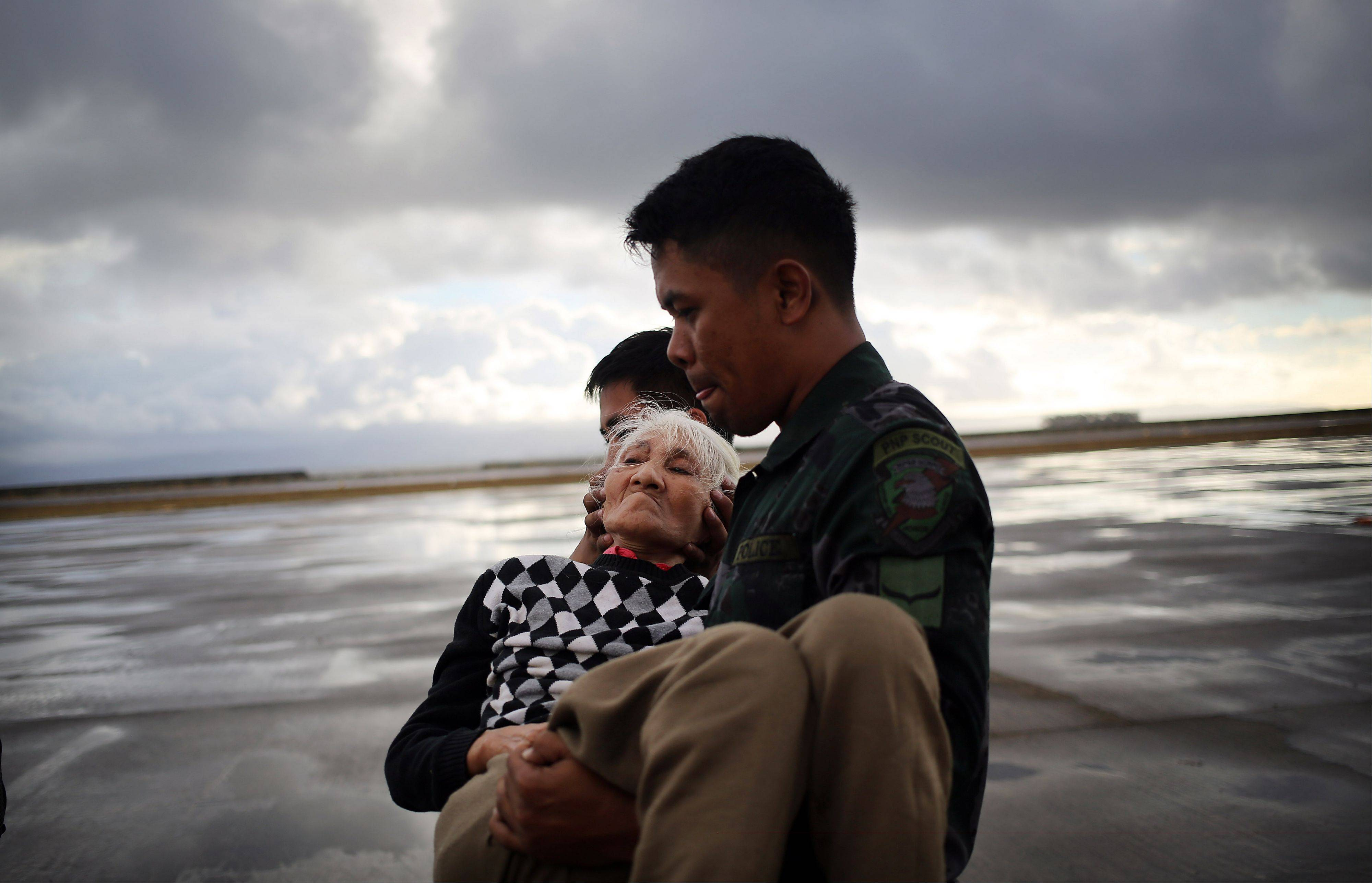 An elderly woman is evacuated from the airport in Tacloban, Wednesday, Nov. 13, 2013 in Tacloban city, Leyte province, central Philippines. Typhoon Haiyan, one of the strongest storms on record, slammed into six central Philippine islands on Friday leaving a wide swath of destruction.