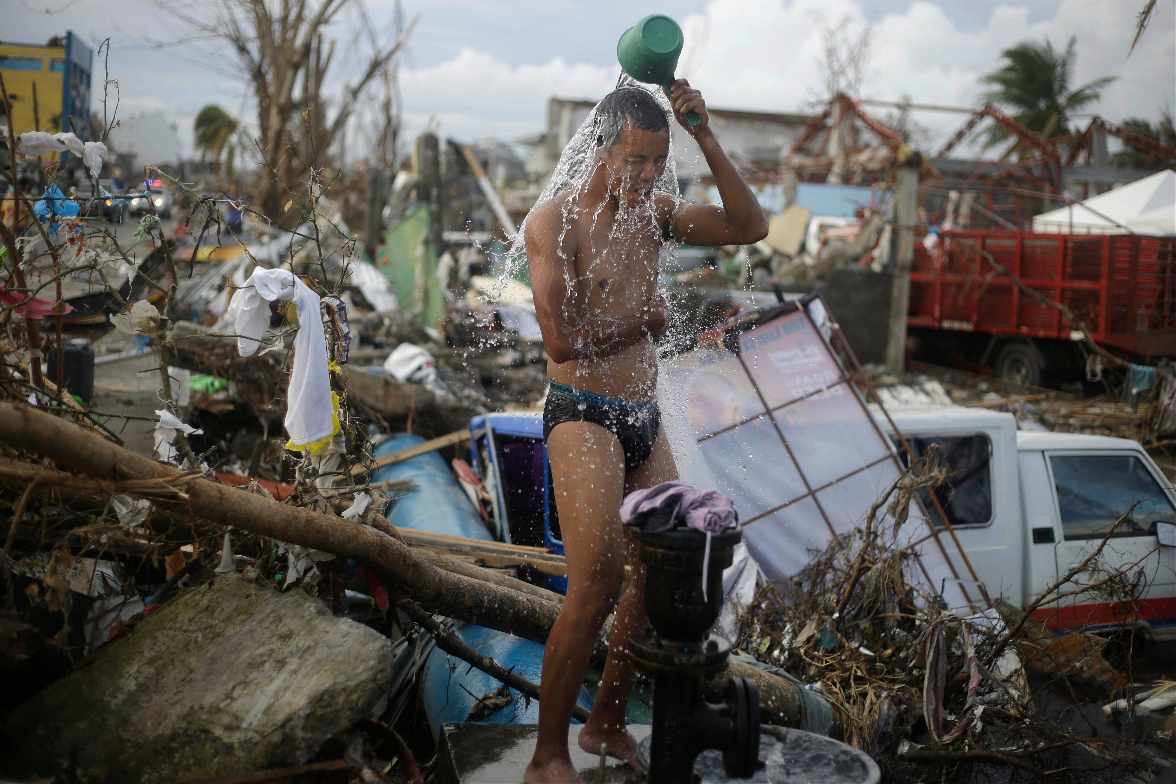 A man takes a shower amid rubble in an area badly affected by Typhoon Haiyan in Tacloban, central Philippines, Wednesday, Nov. 13, 2013. Typhoon Haiyan, one of the strongest storms on record, slammed into six central Philippine islands on Friday, leaving a wide swath of destruction.