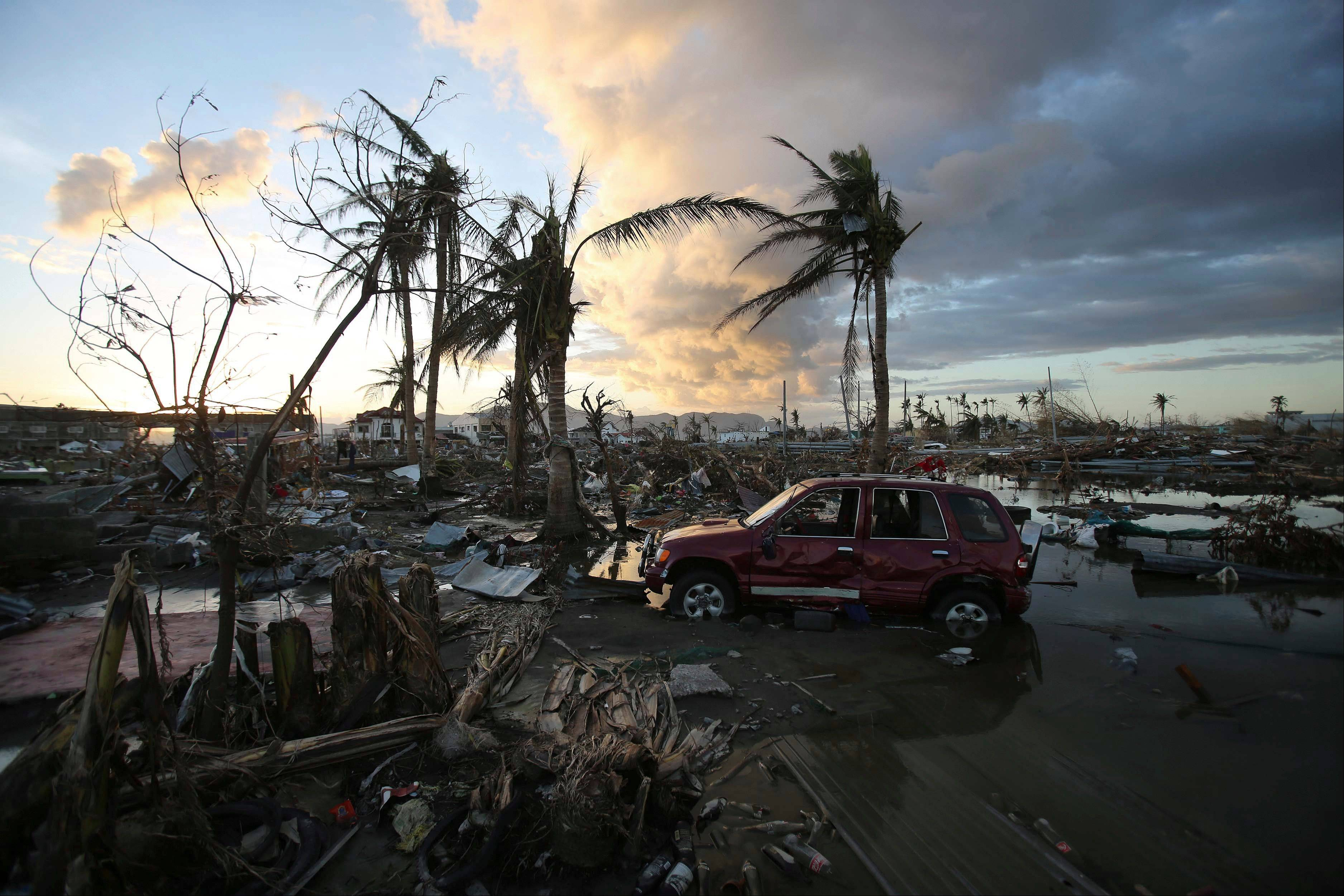 As the sun sets, it lights the sky over the area devastated by Typhoon Haiyan, in Tacloban, central Philippines, Friday, Nov. 15, 2013. Typhoon Haiyan, one of the most powerful storms on record, hit the country's eastern seaboard Nov. 8, leaving a wide swath of destruction.