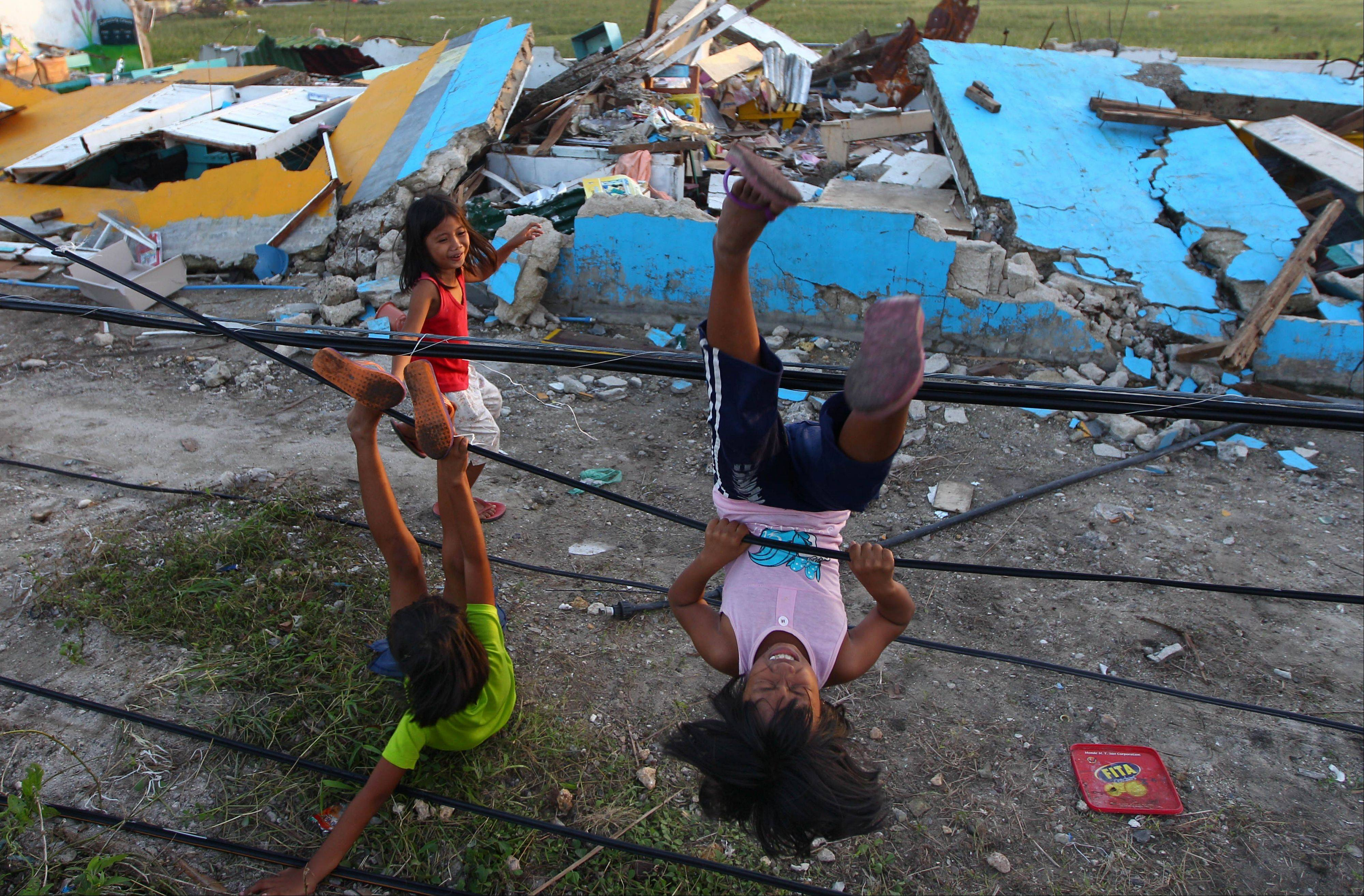 Young survivors of Typhoon Haiyan play with fallen power lines near a damaged school in Guiuan, Philippines, Thursday, Nov. 14, 2013. Typhoon Haiyan, one of the most powerful storms on record, hit the country's eastern seaboard on Friday, destroying tens of thousands of buildings and displacing at least a half-million people.
