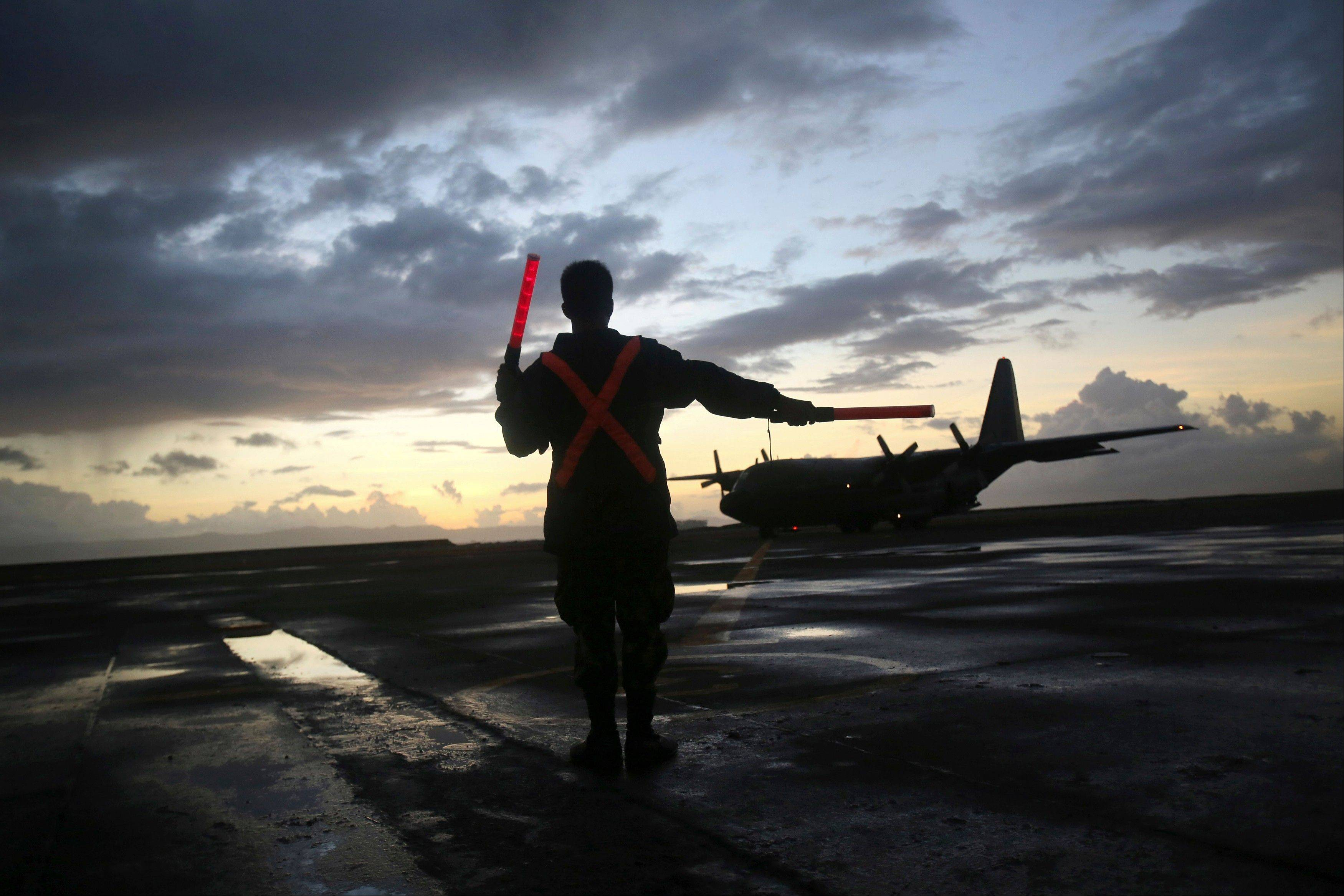 A military C-130 lands to evacuate survivors of Typhoon Haiyan at dusk, Friday, Nov. 15, 2013 in Tacloban city, Leyte province, central Philippines. Typhoon Haiyan, one of the most powerful storms on record, hit the country's eastern seaboard Nov. 8, leaving a wide swath of destruction.