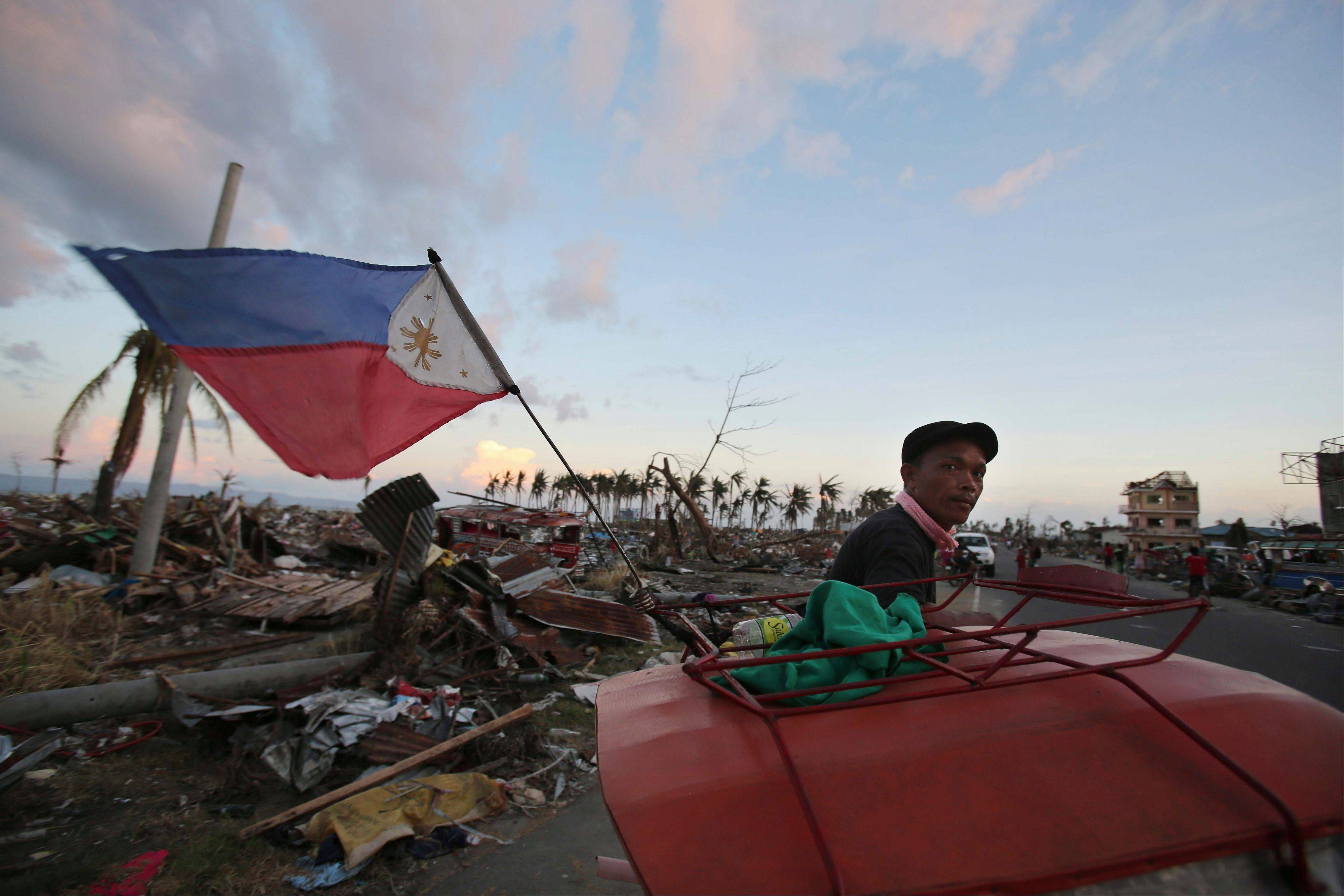 A Filipino pedicab driver pedals past damaged homes at typhoon hit Tacloban city, Leyte province, central Philippines on Friday, Nov. 15, 2013. Typhoon Haiyan, one of the most powerful storms on record, hit the country's eastern seaboard Nov. 8, leaving a wide swath of destruction.